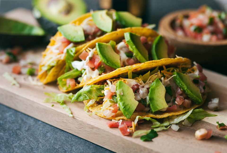 Ground beef tacos with avocado on cutting board.
