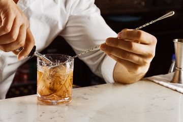 Bartender using a barspoon to make a drink.