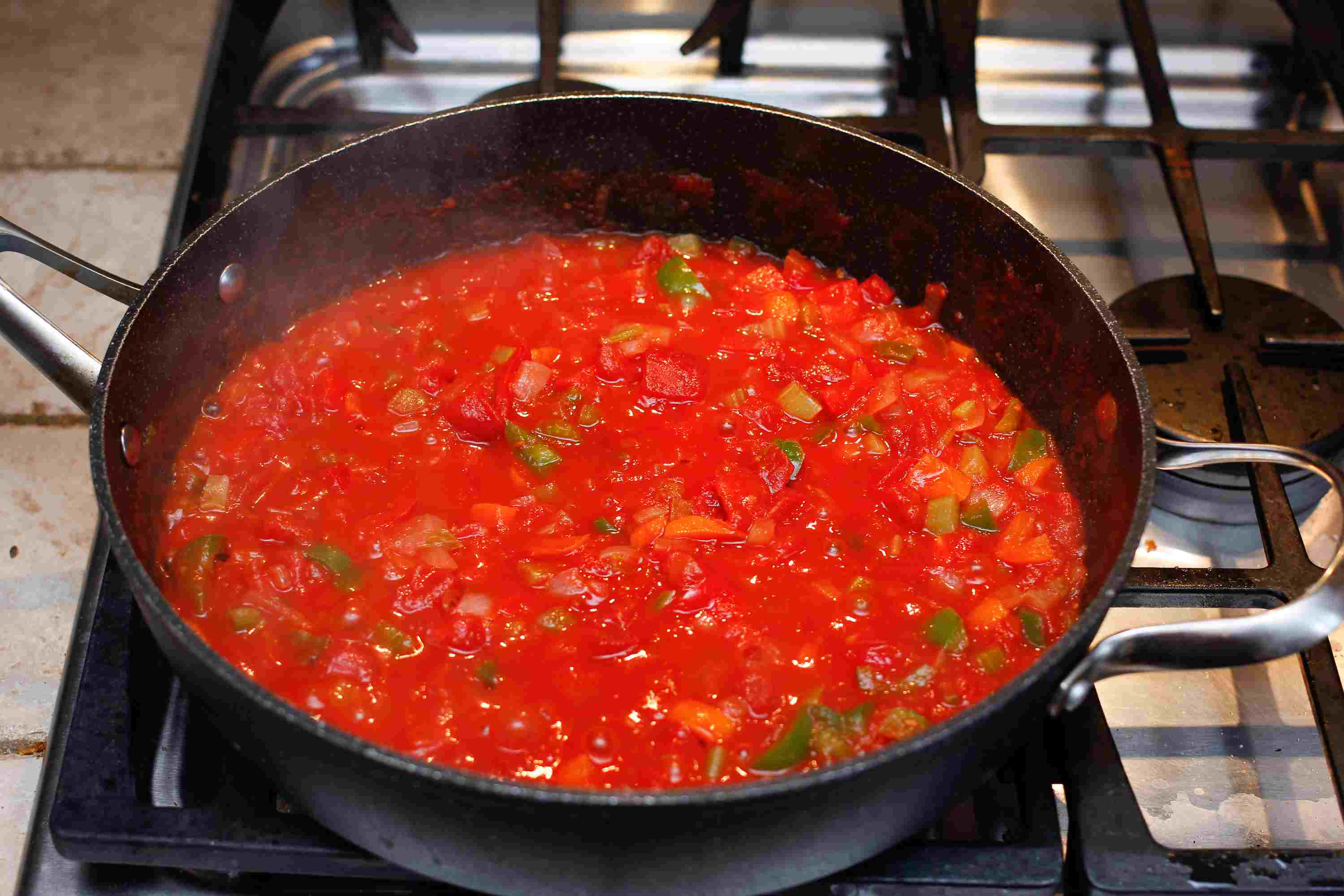 Tomatoes and tomato sauce in a saucepan with chopped veggies