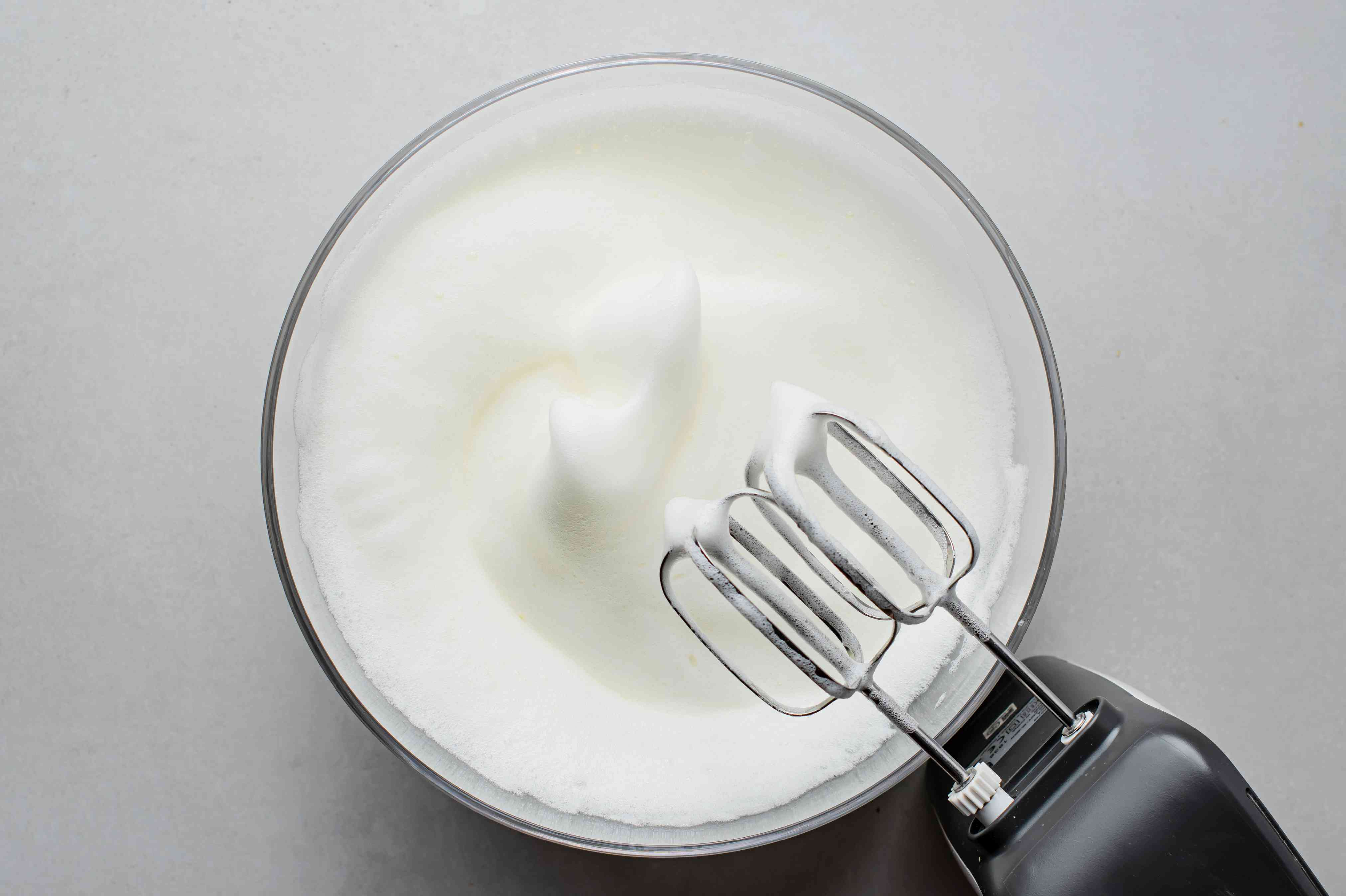 egg whites beat with a hand mixer in a bowl