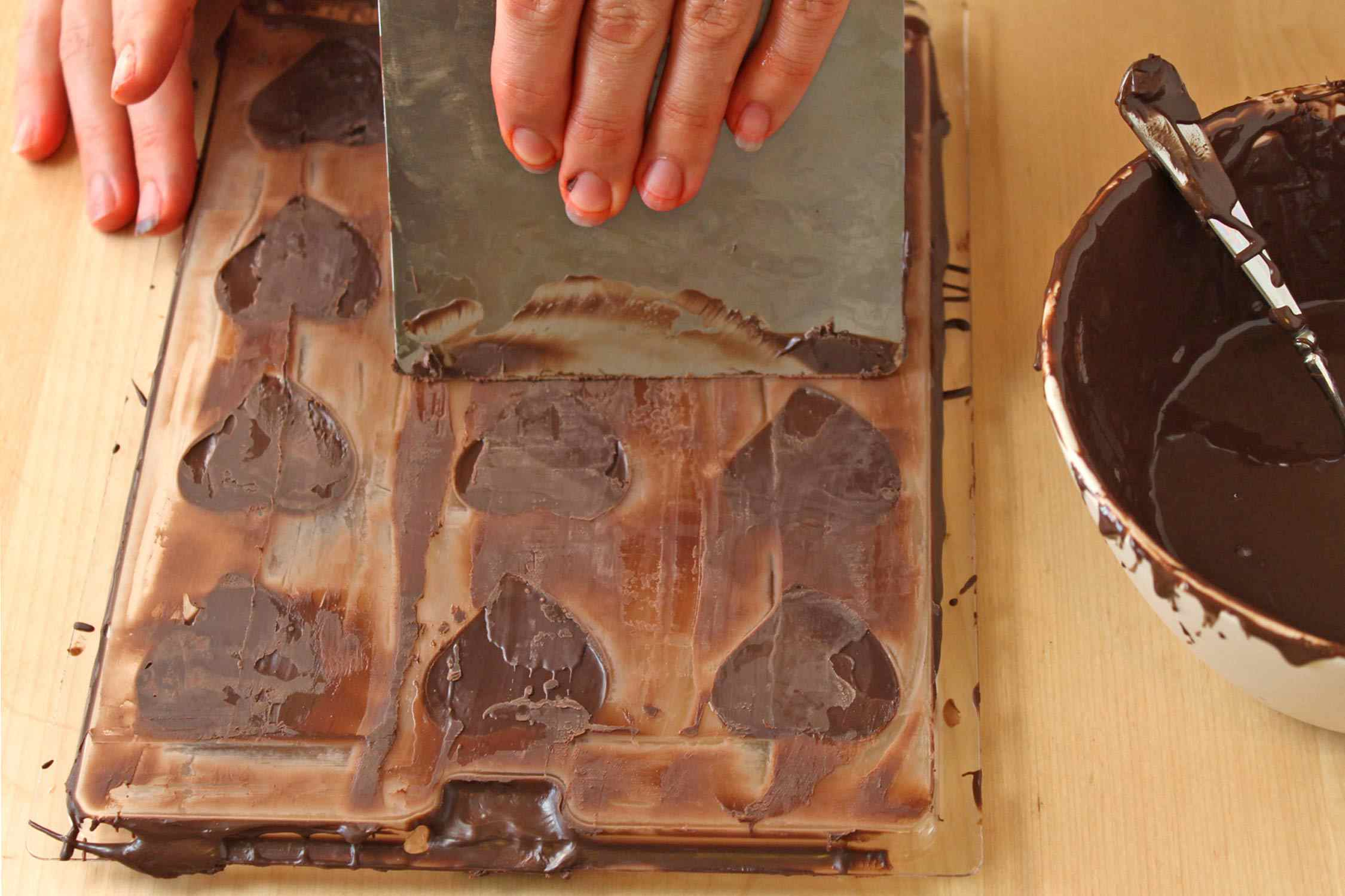 Scraping chocolate from top of chocolates in candy mold