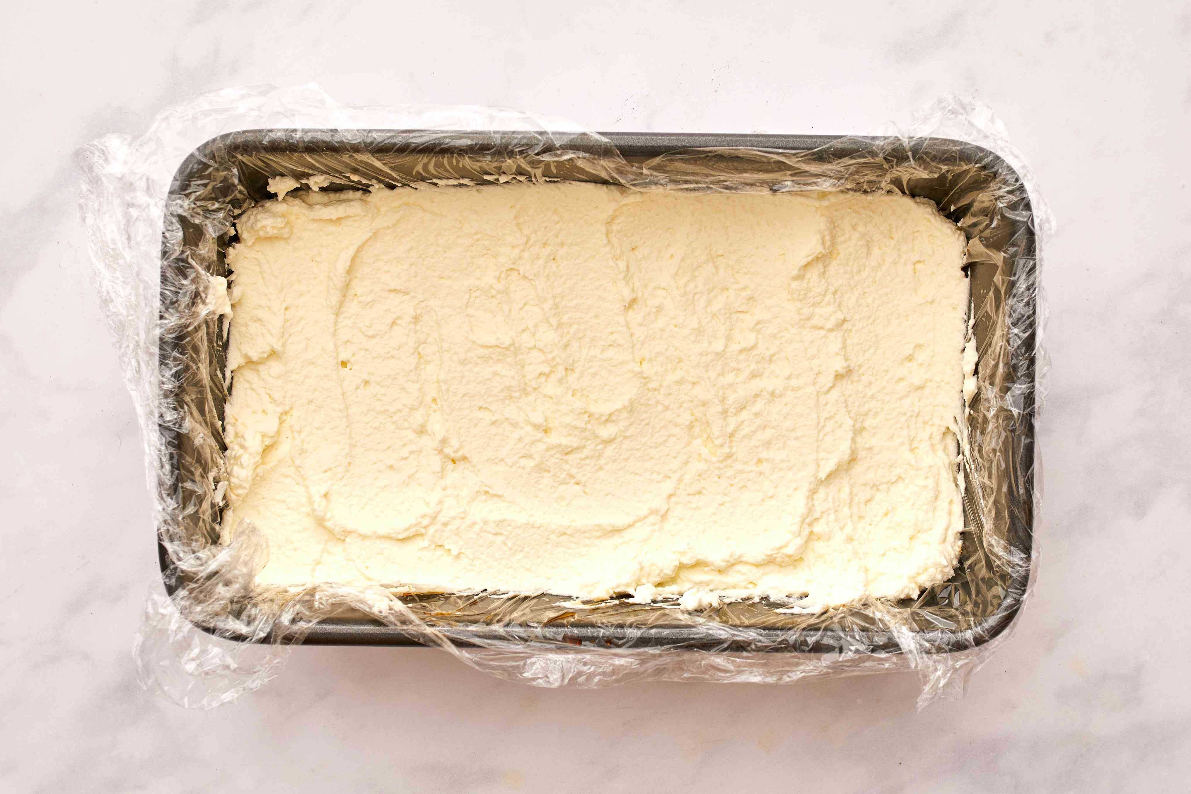 cream mixture layered on ladyfingers in loaf pan