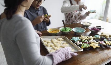 Woman bringing a fresh tray of cookies to her kids icing