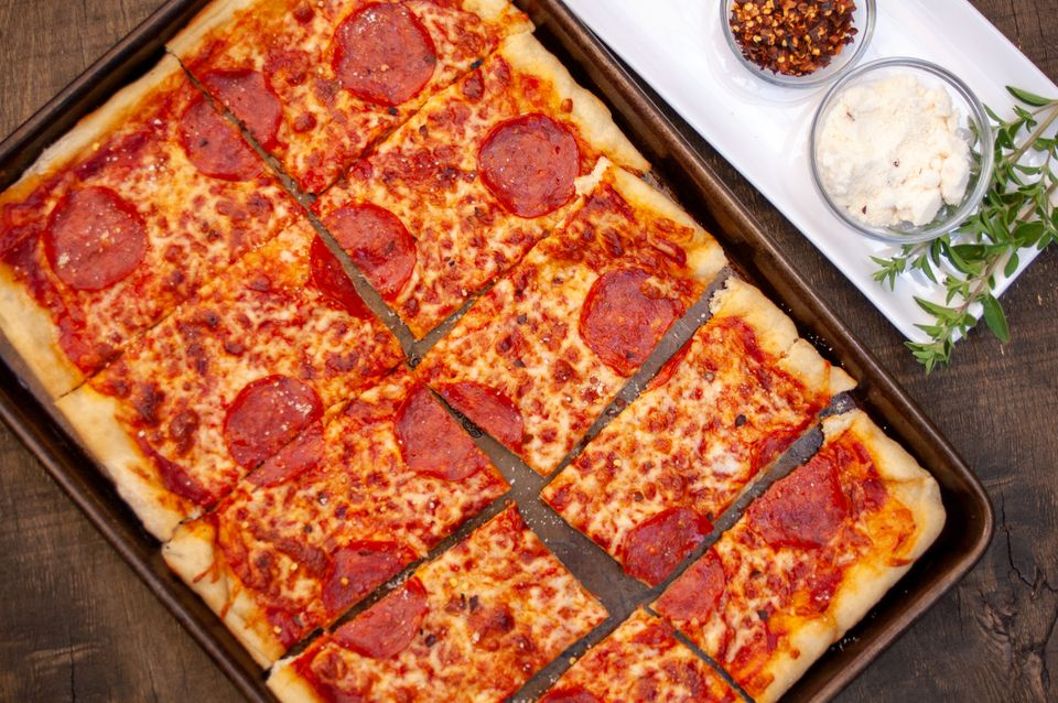 sheet pan pizza with seasonings on the side