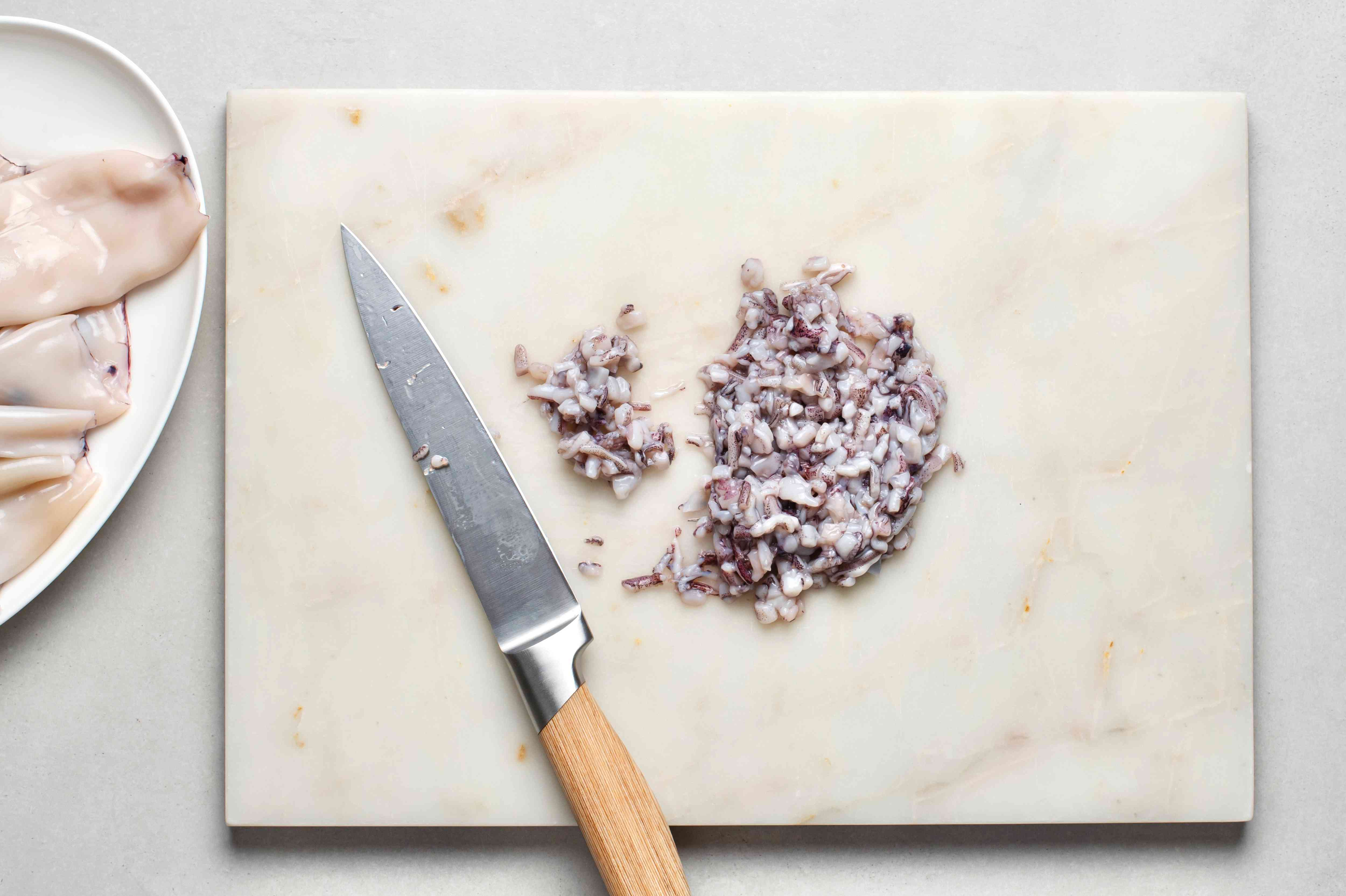 A cutting board with chopped squid tentacles