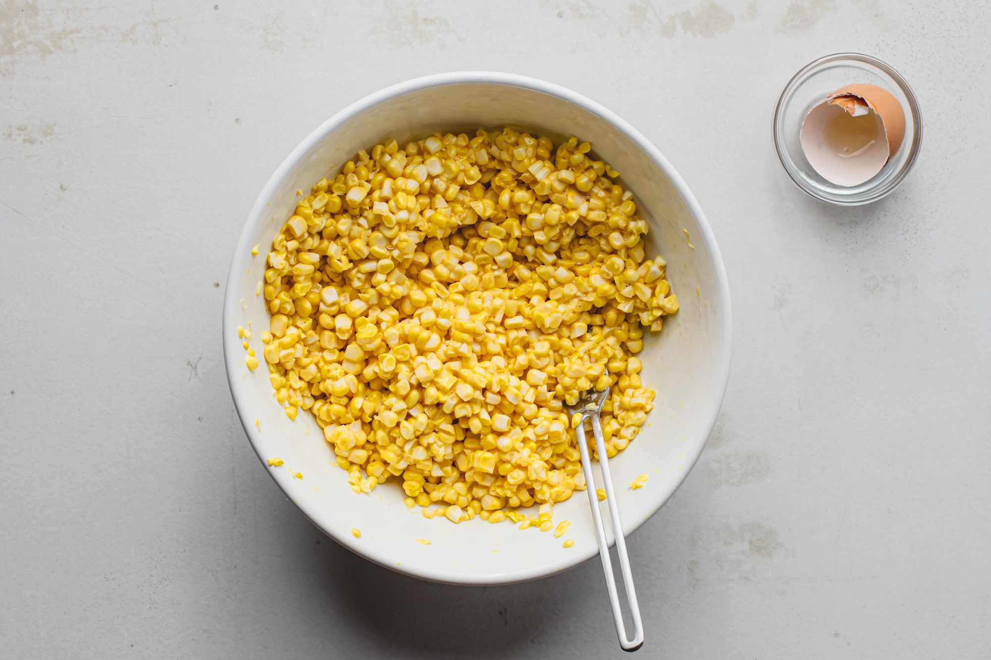 Corn kernels in a bowl with egg added