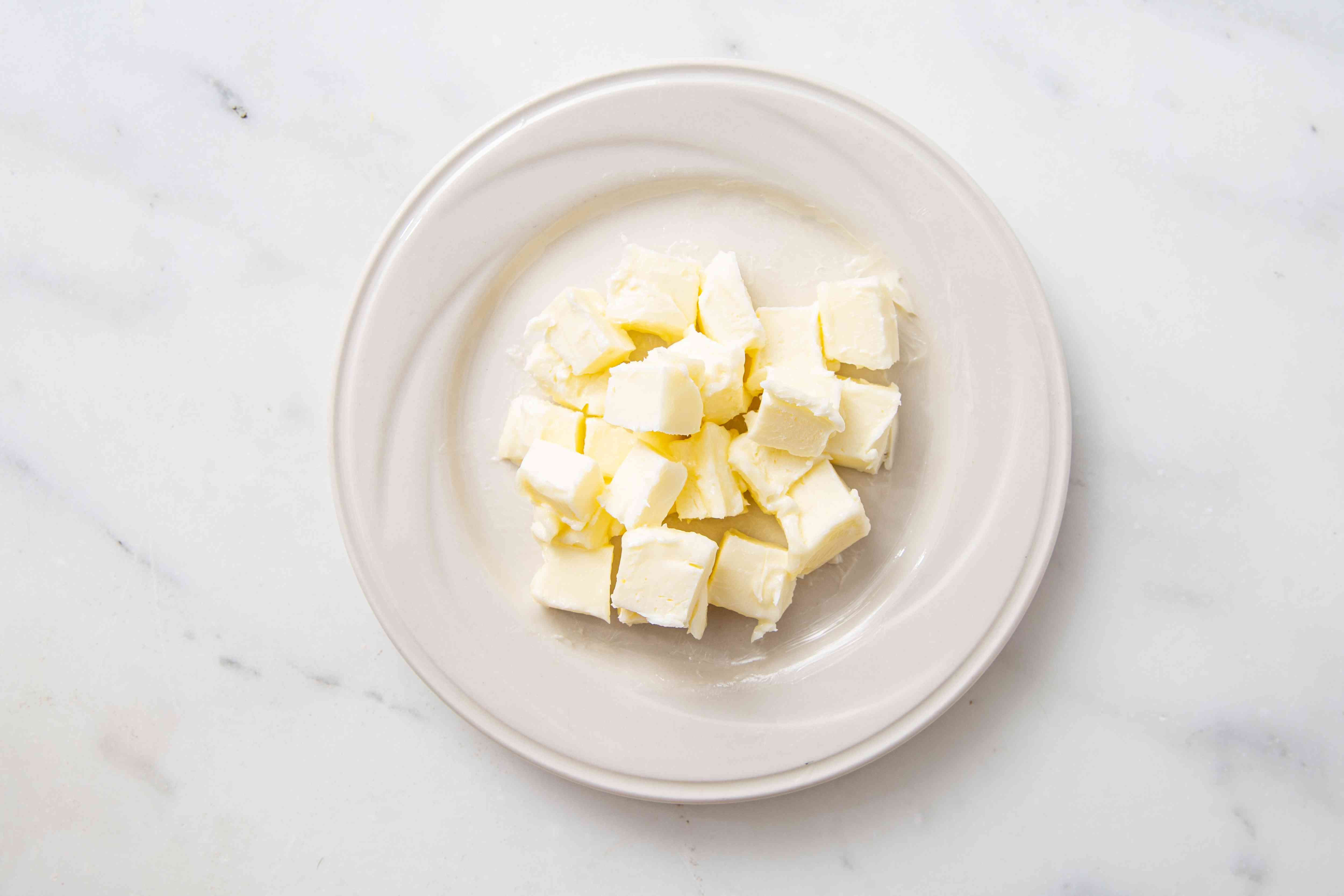 Cut-up butter on a white plate