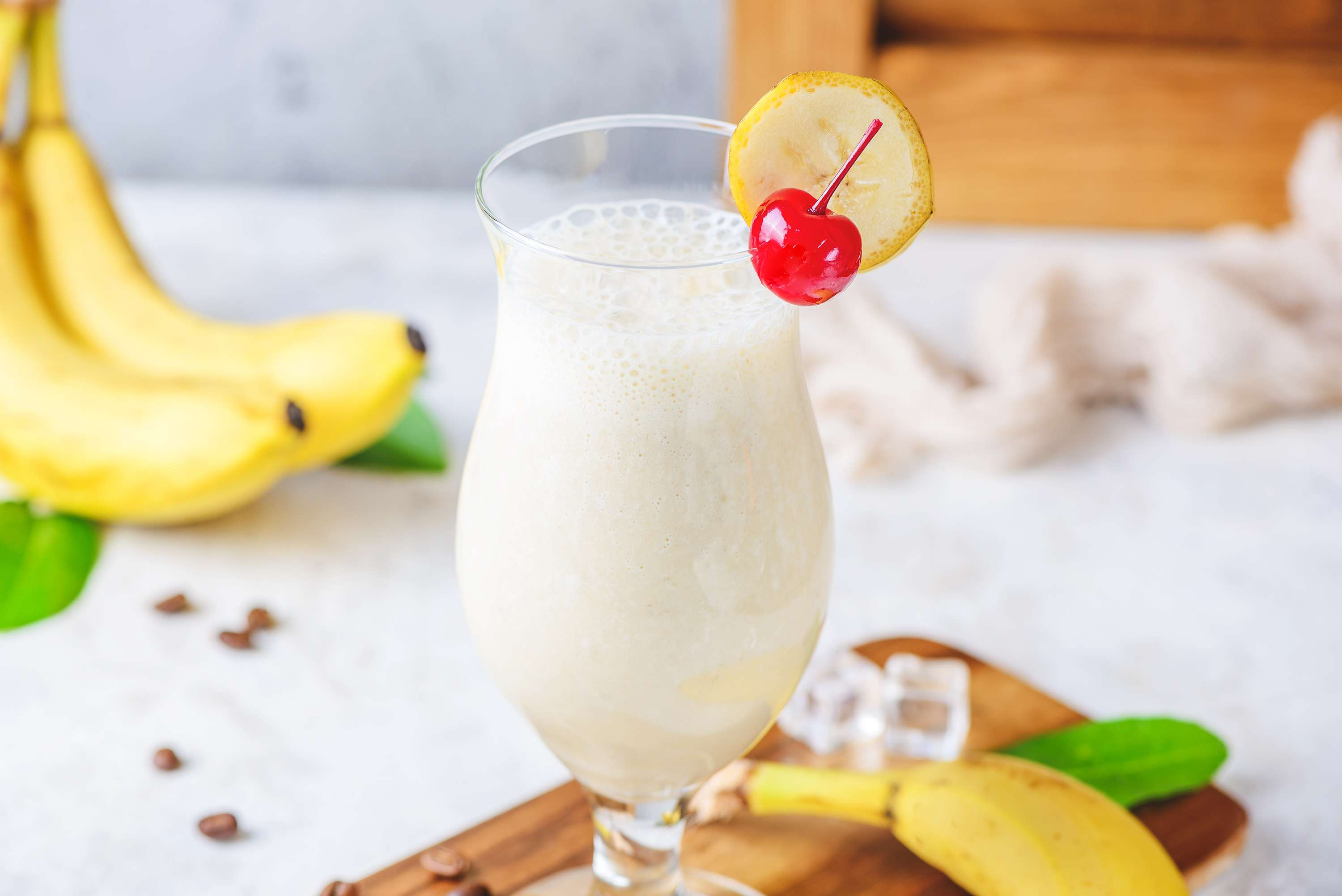 Banana wheel and cherry hanging on the rim of the glass