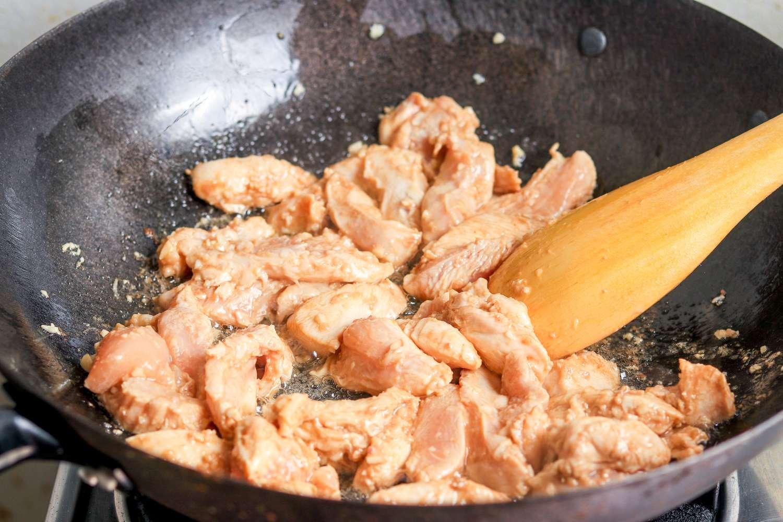Cook garlic and chicken in wok