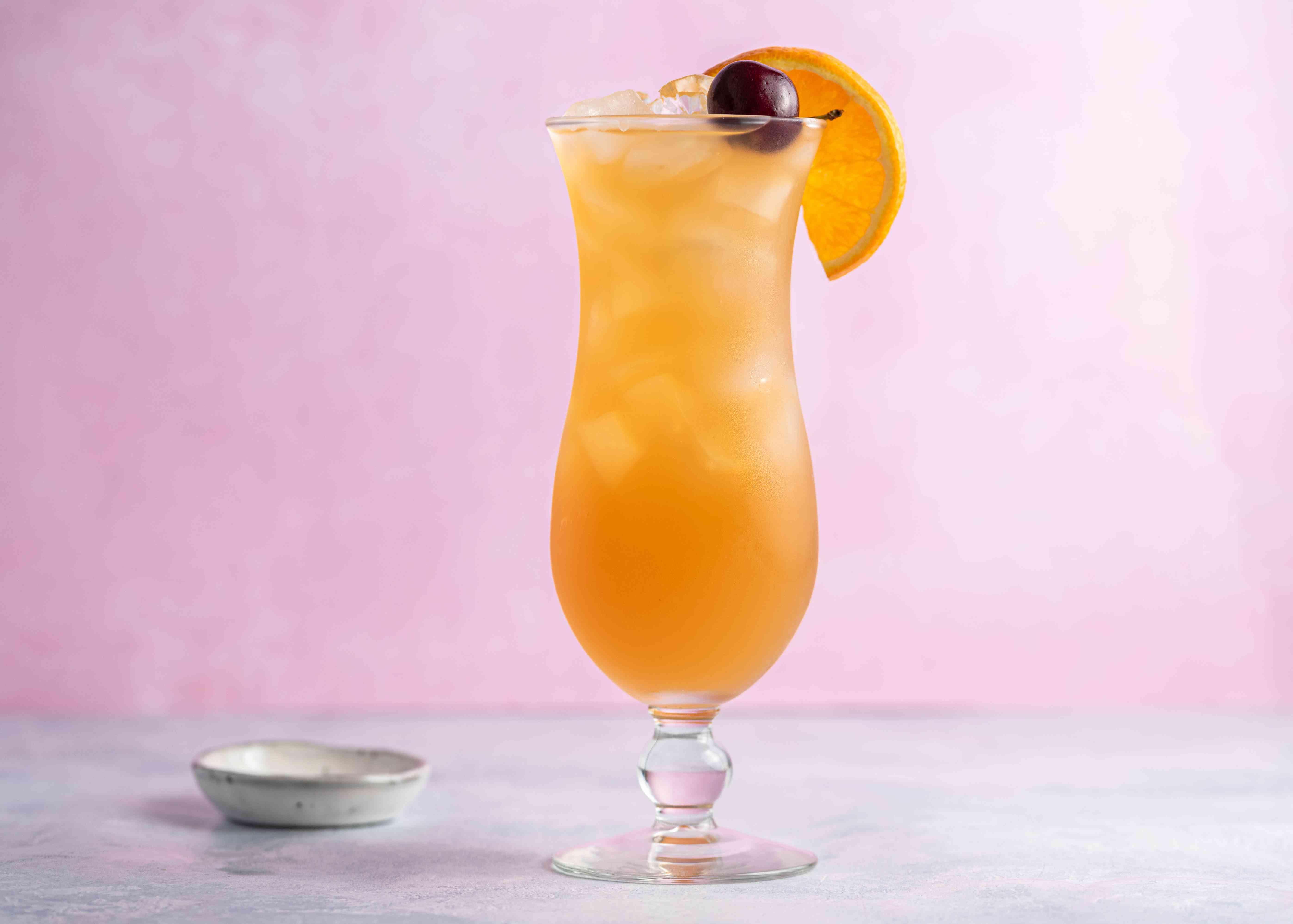 Hurricane cocktail with a cherry and orange slice garnish