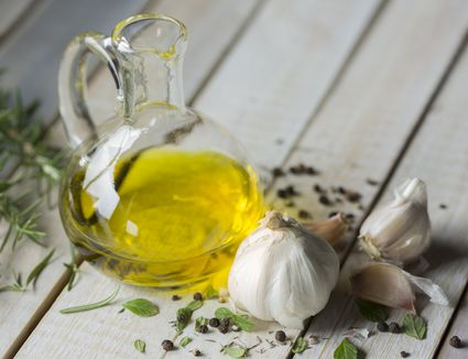 Olive oil in a cruet, garlic, and herbs