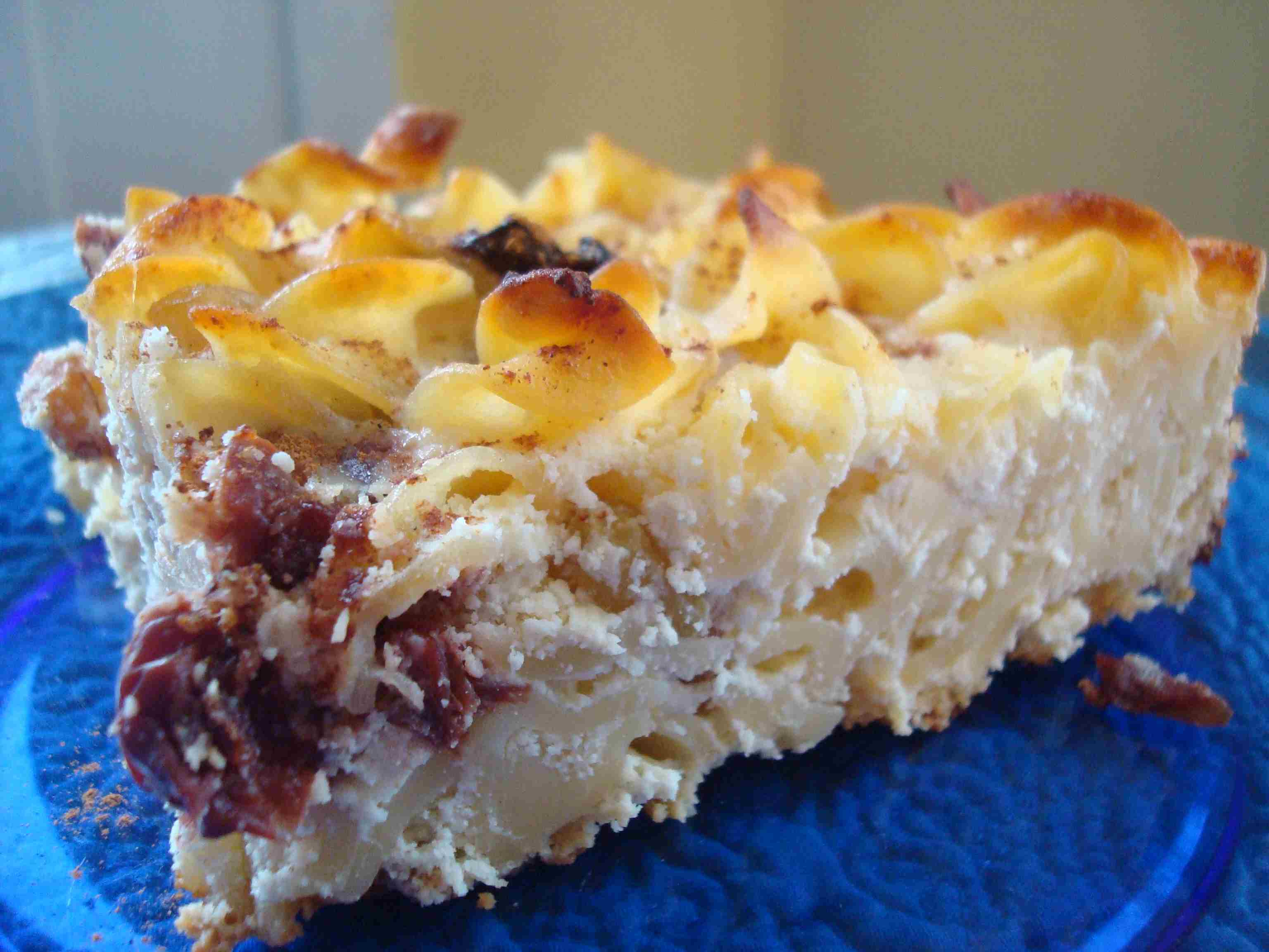 A portion of kugel made with ricotta cheese and dried cherries on a plate