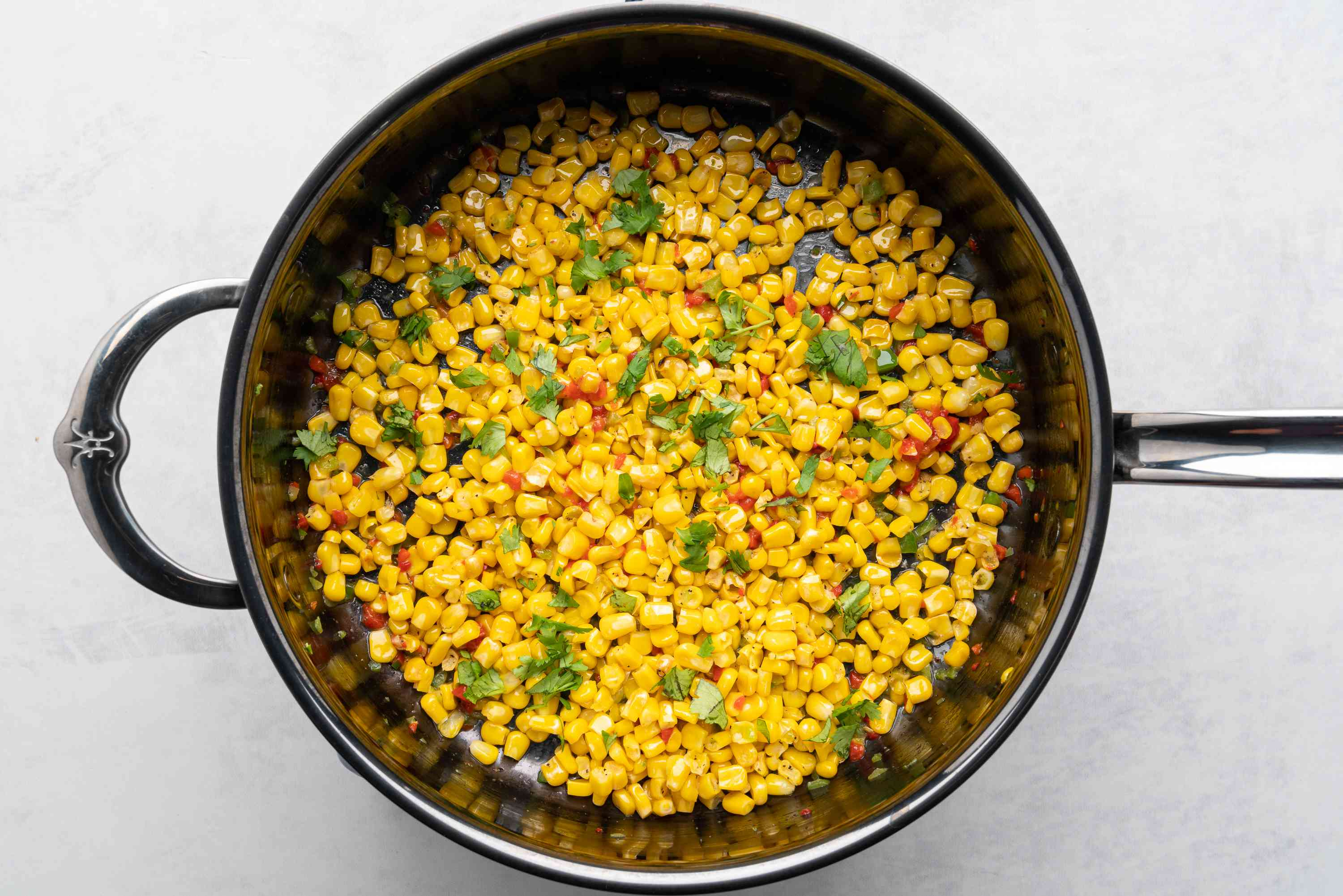 Mexican-Style Corn With Peppers i na skillet with cilantro
