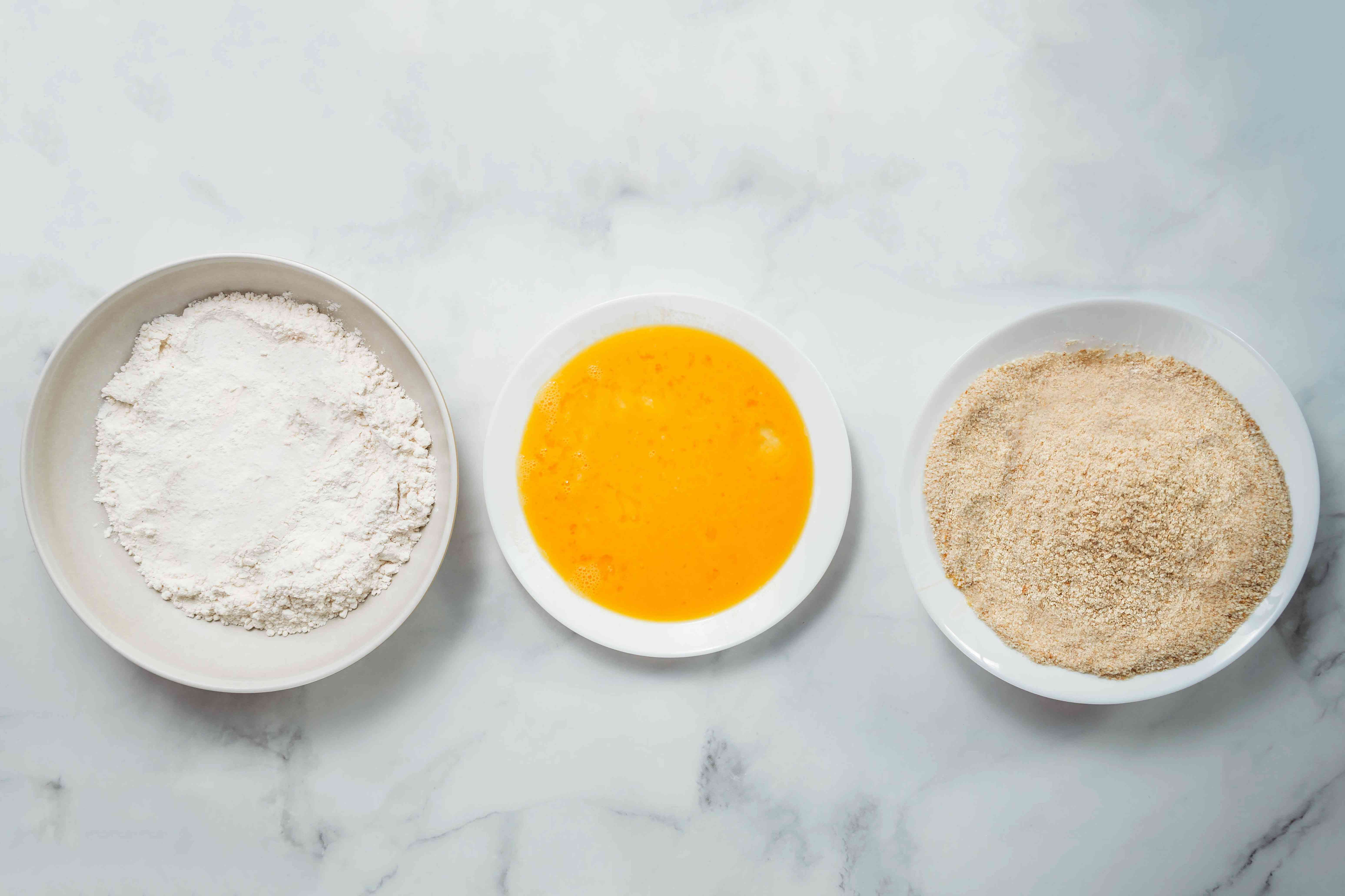 Three separate bowls: flour, egg mixture, and breadcrumbs