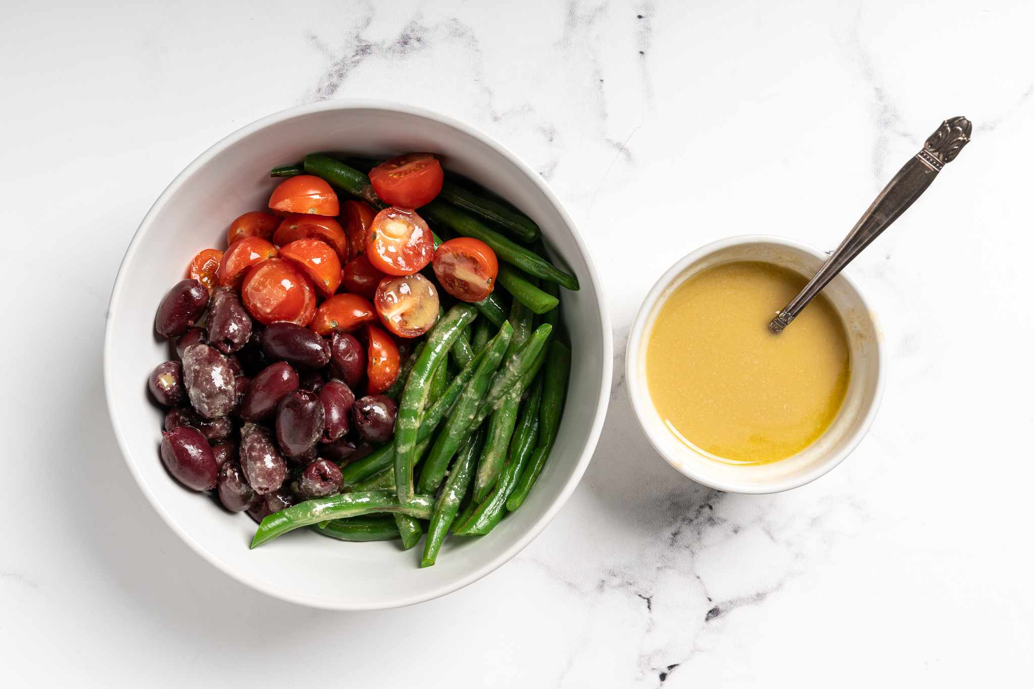vegetables in a bowl, dressing in a bowl