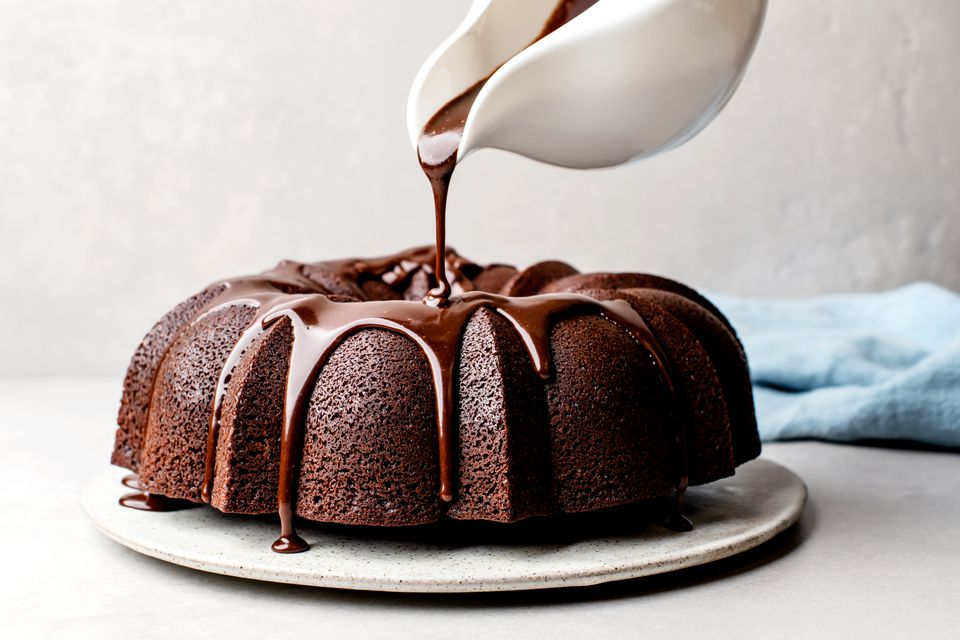 Pouring chocolate glaze over a chocolate Bundt cake