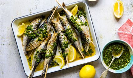 A dish of skewered sardines with lemons