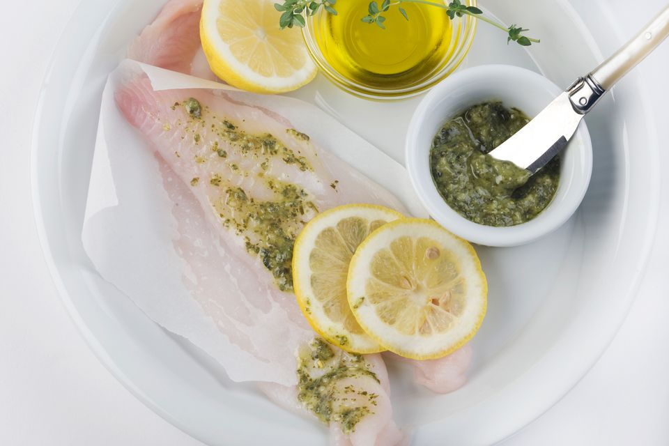 flounder or sole on a white background with lemon, oil and pesto