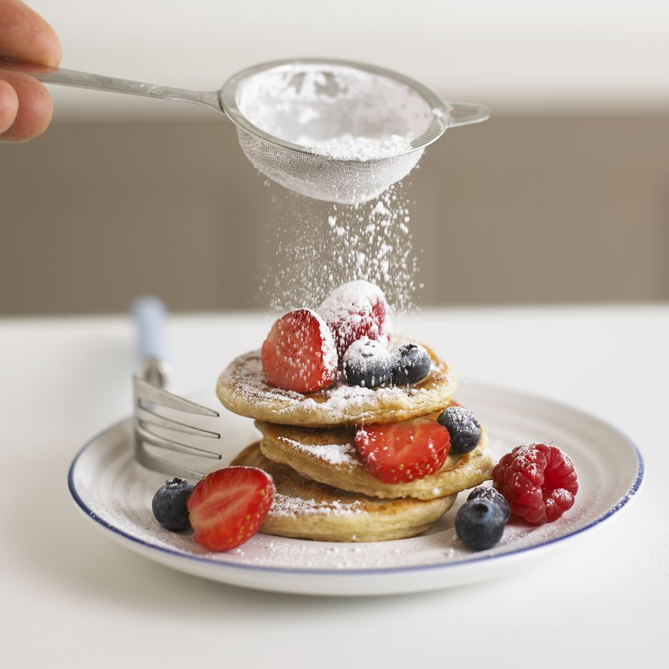 Sifting icing sugar onto fruit and pancakes