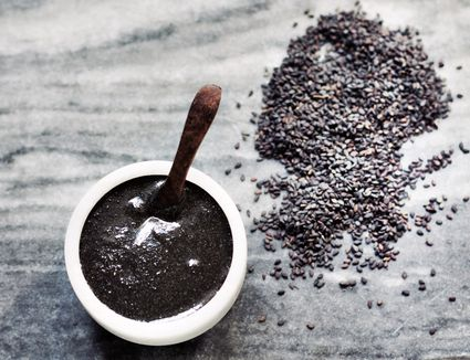 Black sesame seeds ground into tahini with a mortar and pestle
