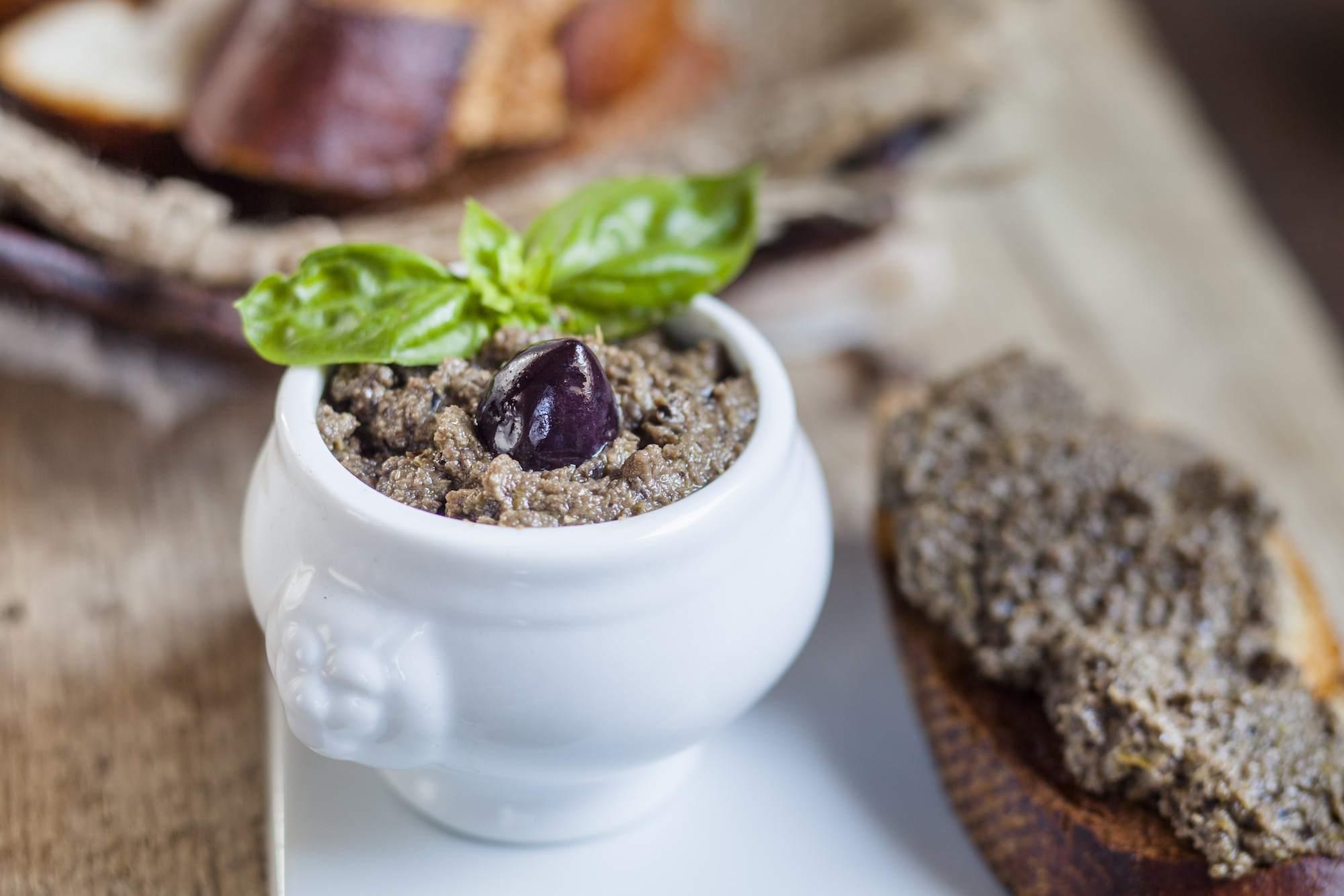 Black tapenade in bowl, crostini with olive paste