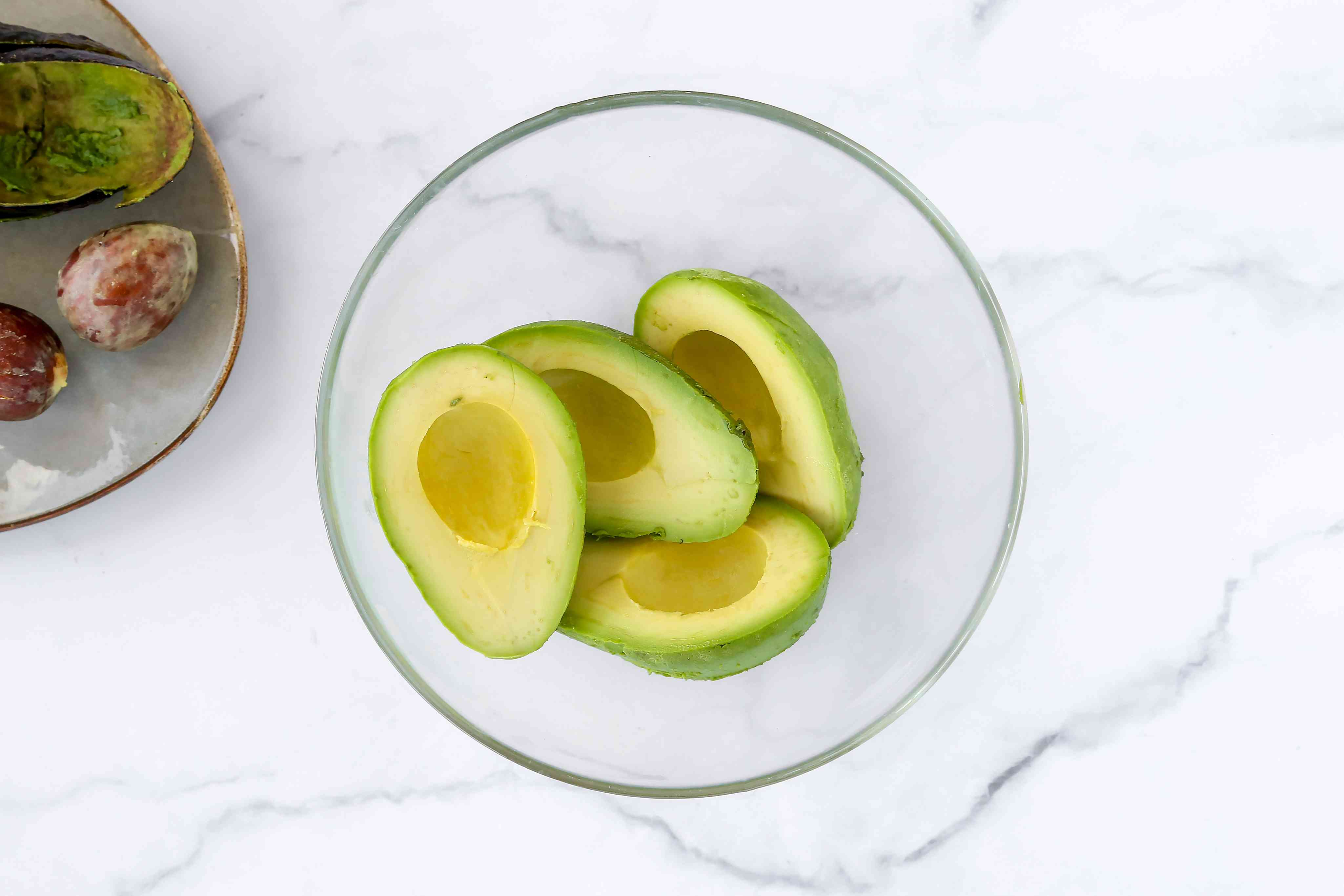 Remove the pit from the avocados and put the flesh into a mixing bowl