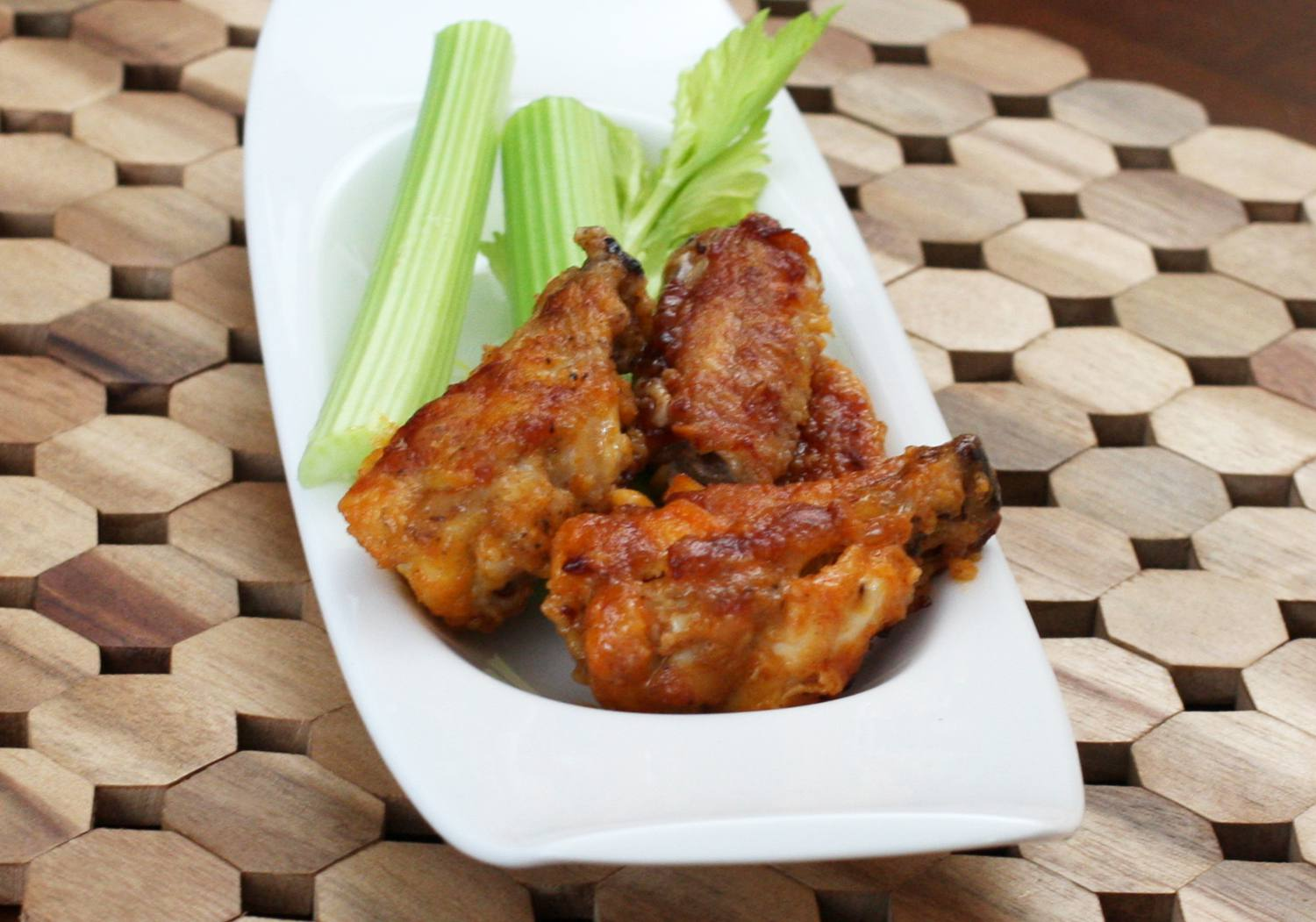 Spicy baked chicken wings in an oval-shaped white bowl with celery sticks