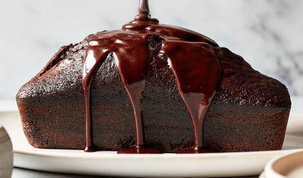 pouring chocolate glaze over a chocolate loaf cake