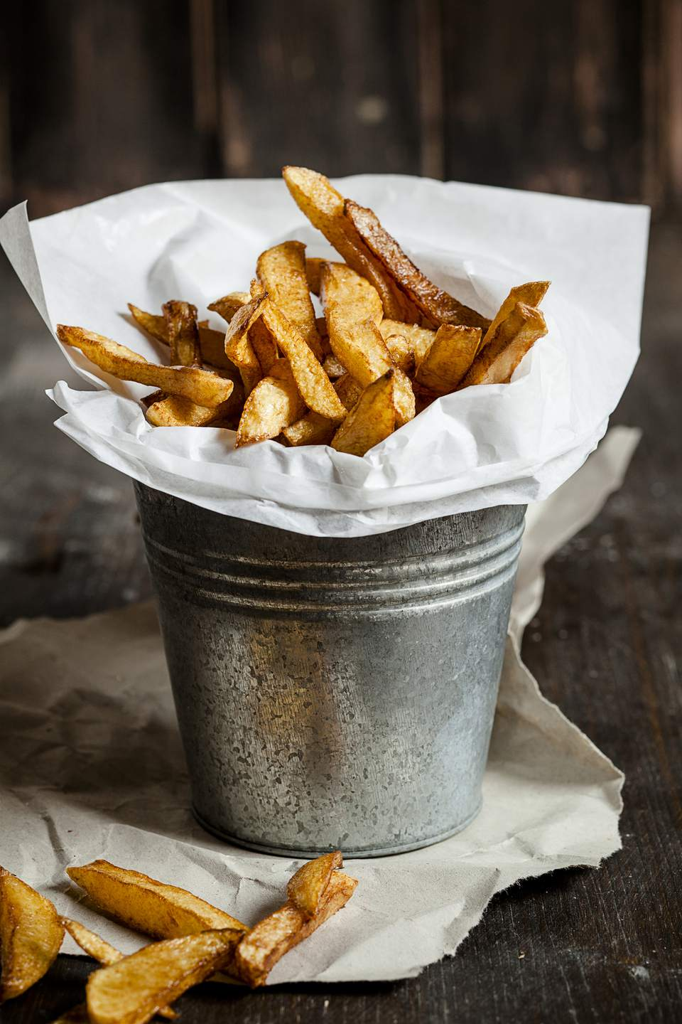 Fresh french fries in a tin and paper