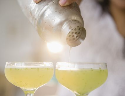 a woman pouring a yellow drink into two glasses