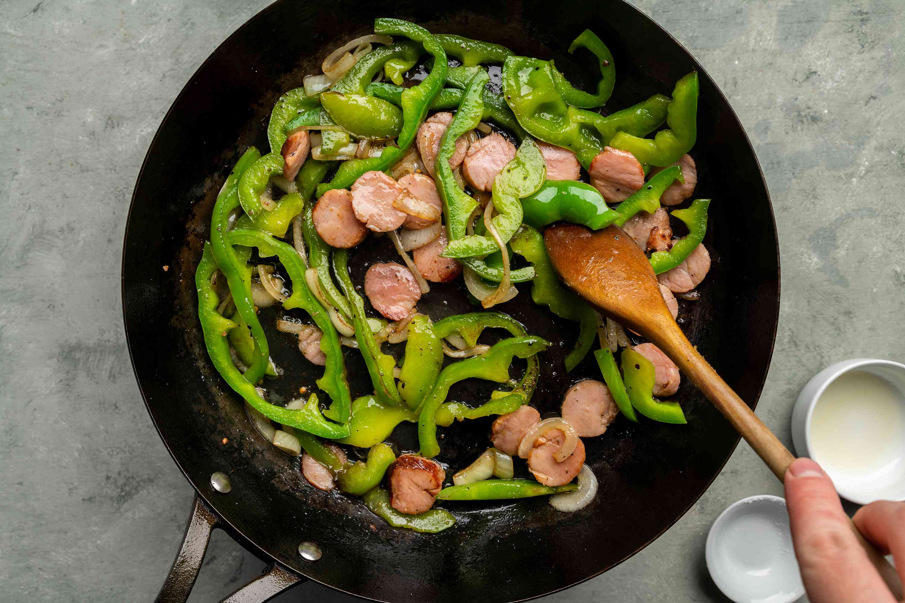 onion, bell pepper, and sausage cooking in a skillet