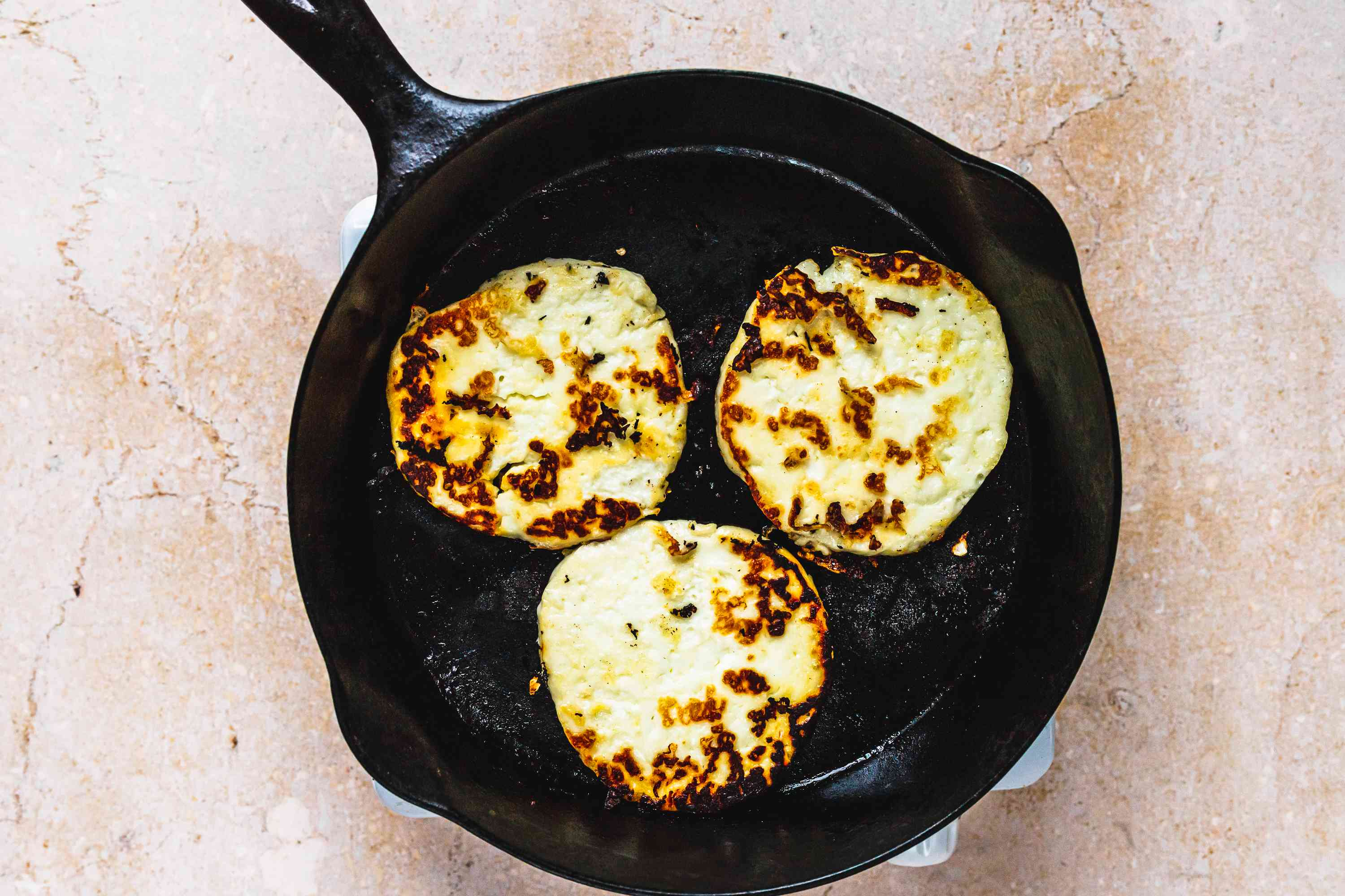 Halloumi cheese slices browning in pan