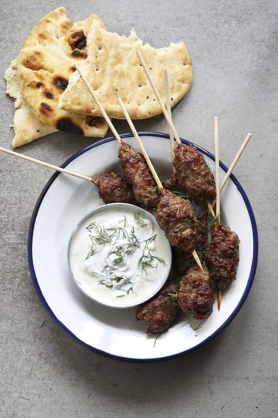 Turkish Kofta on an enamel plate with dill yogurt dressing