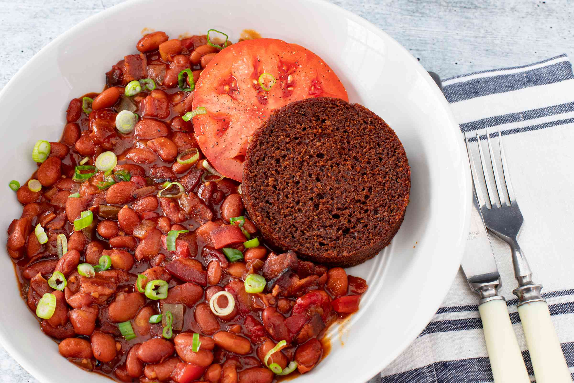 instant pot baked beans with a slice of boston brown bread and tomato