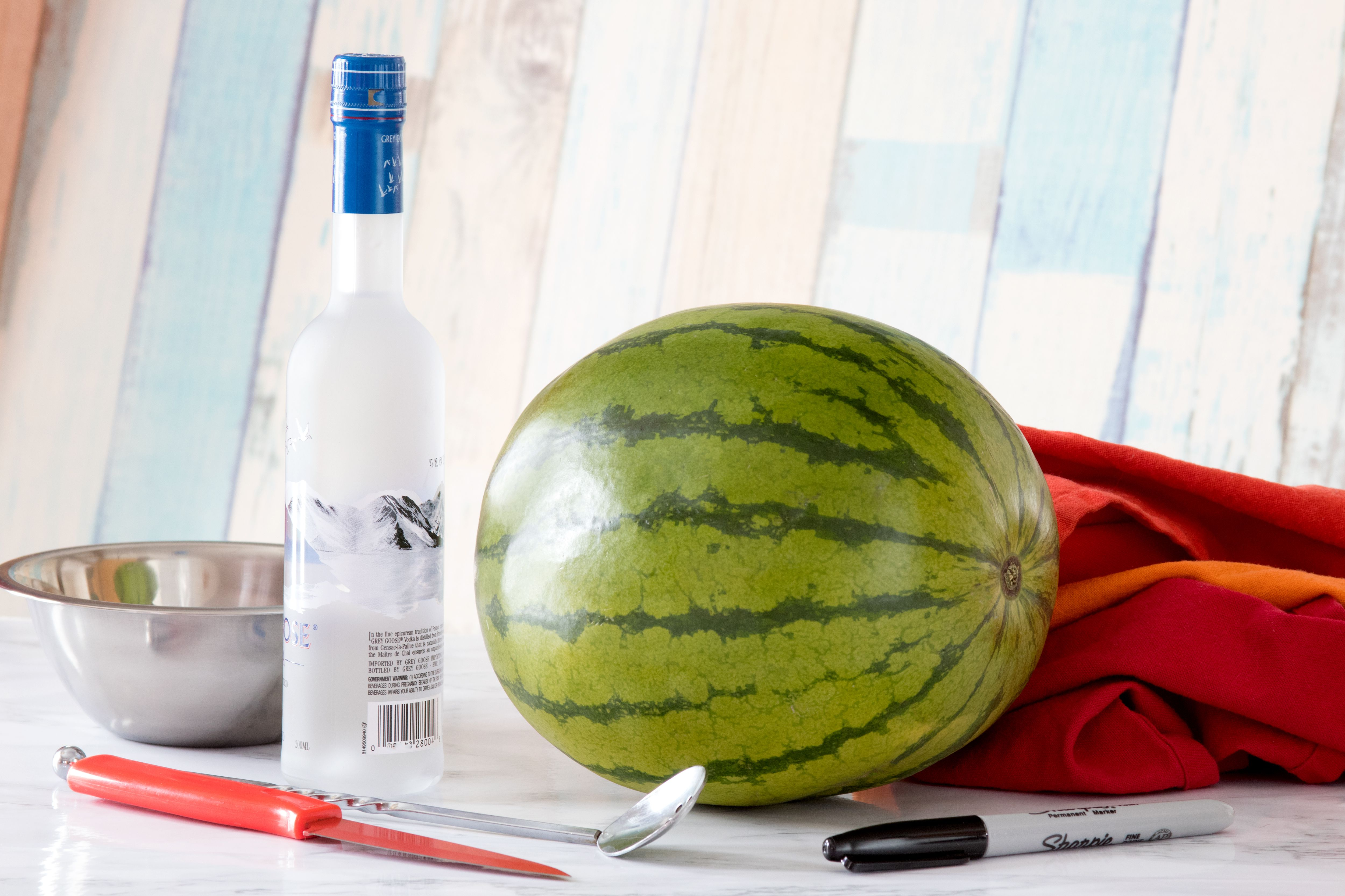 Ingredients and tools for making vodka-spiked watermelon