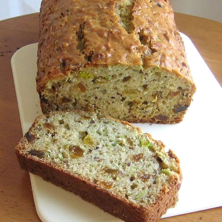 Green tomato quick bread loaf sliced on a cutting board