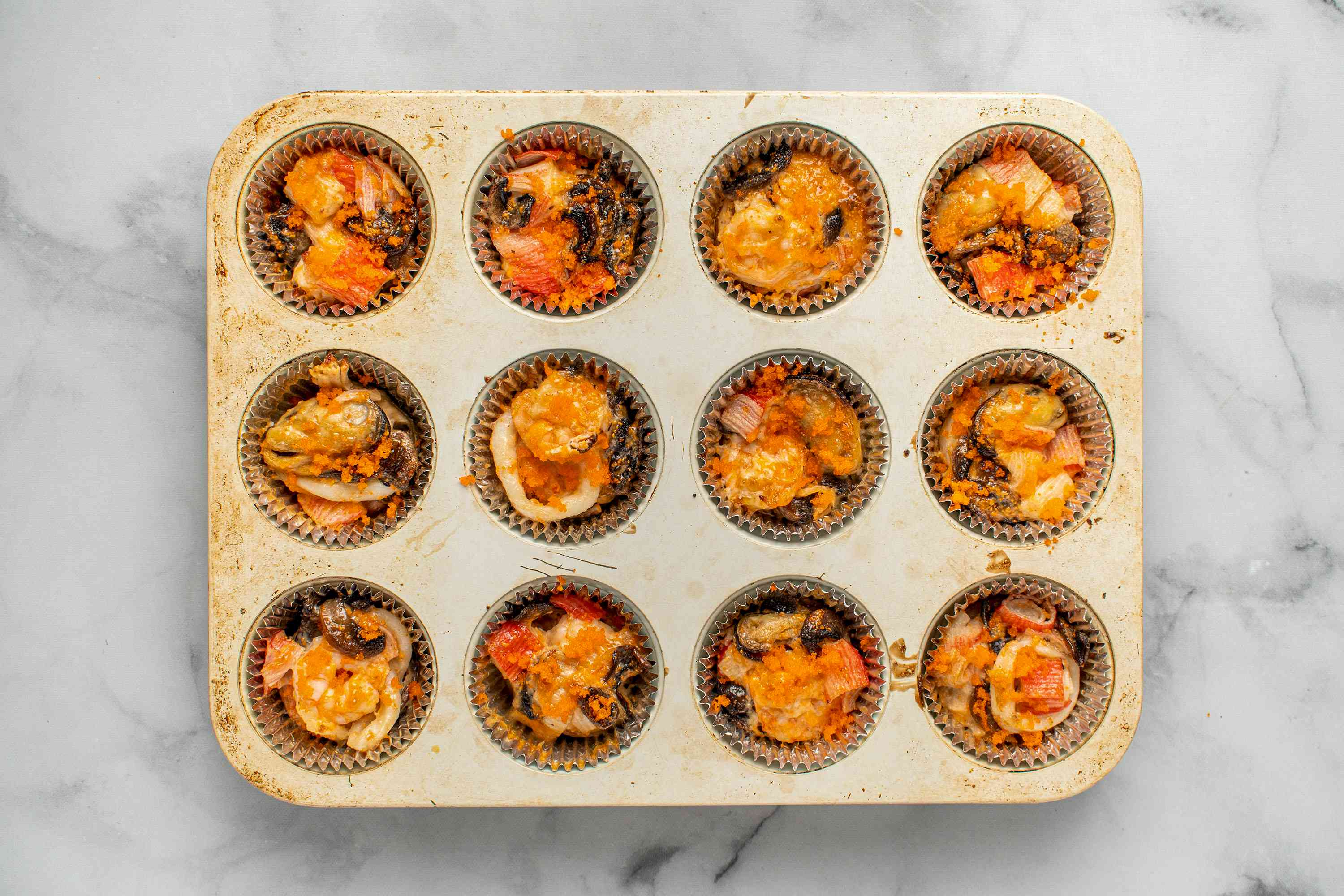 Japanese Baked Dynamite Appetizers with masago on top, in muffin tins