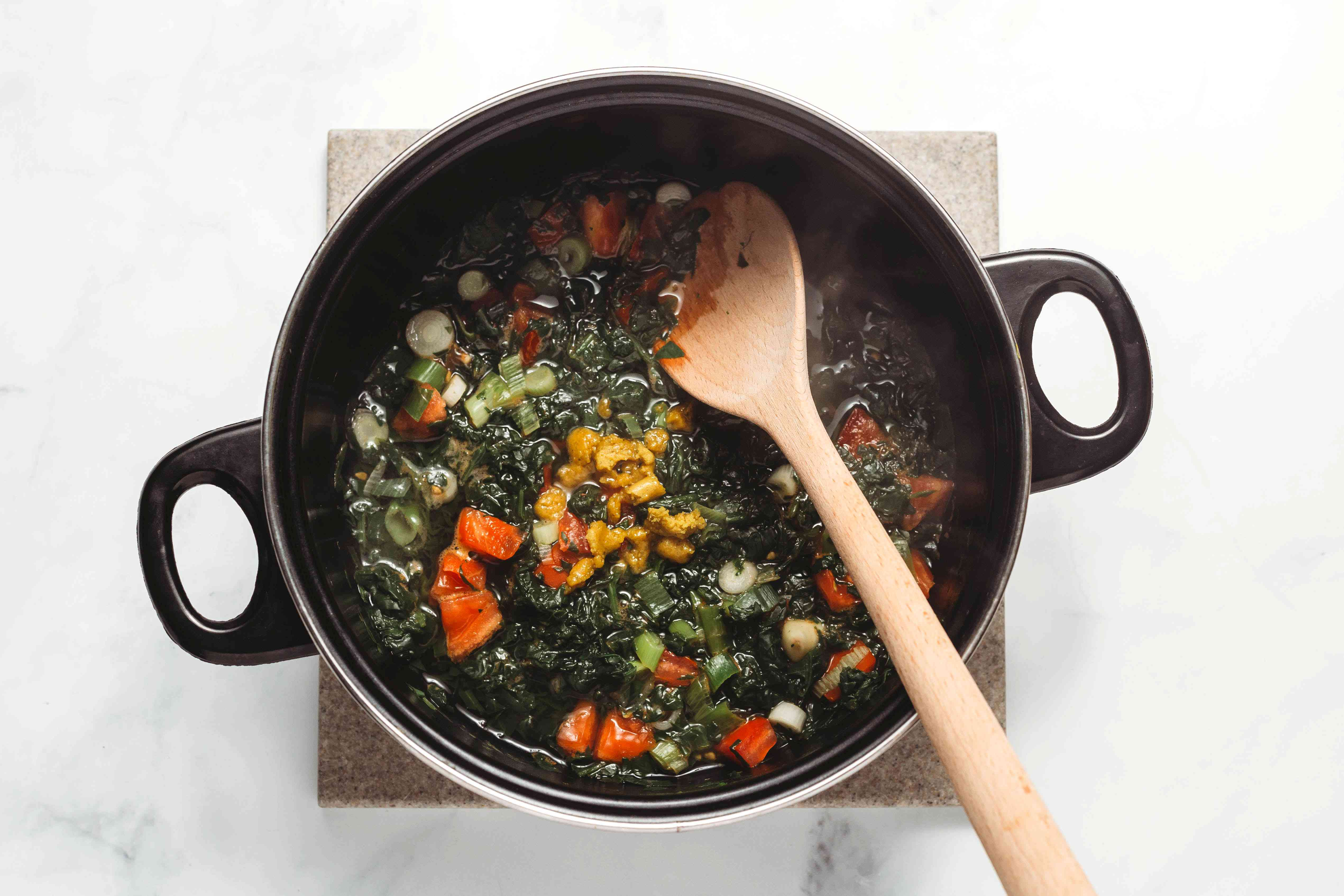 spinach, tomatoes, onions, garlic and stock cube in a large pot with a wooden spoon
