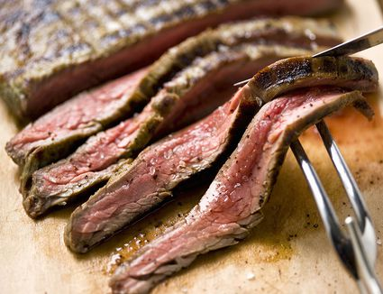 Sliced Steak on Cutting Board With Carving Utensils, Close-Up