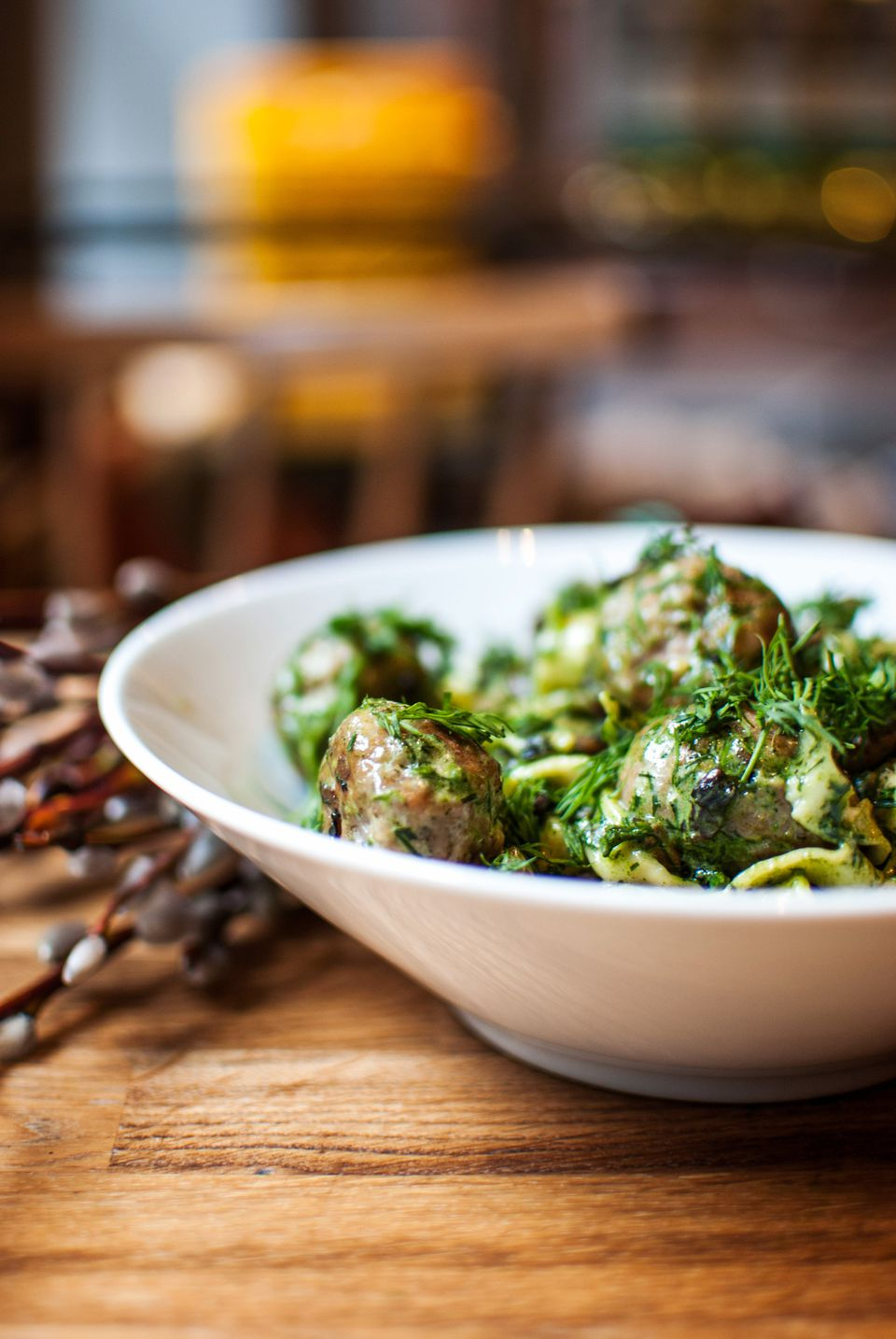 Pesto meatballs in a white bowl on a wooden surface