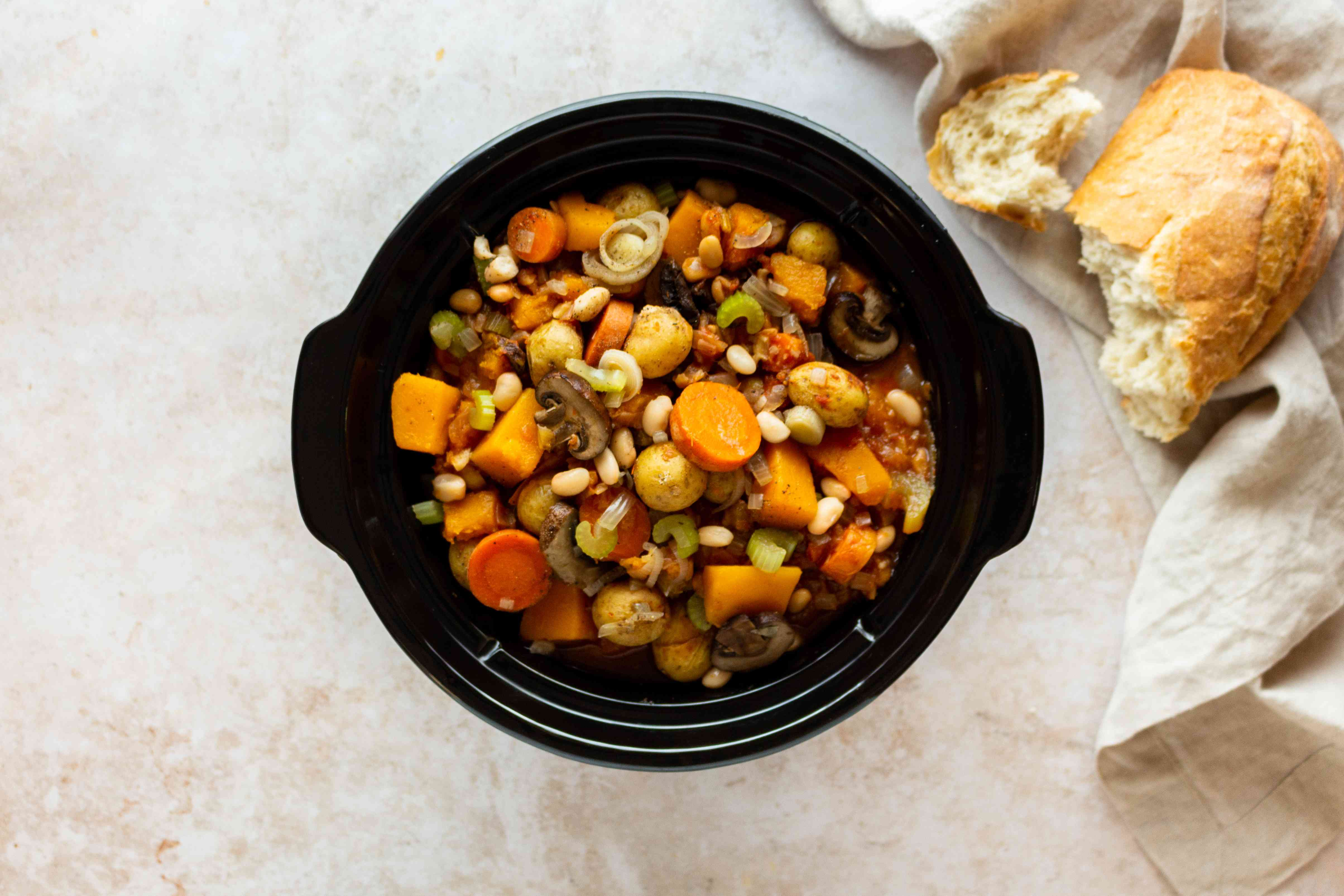 Finished slow cooker vegetable stew with piece of bread