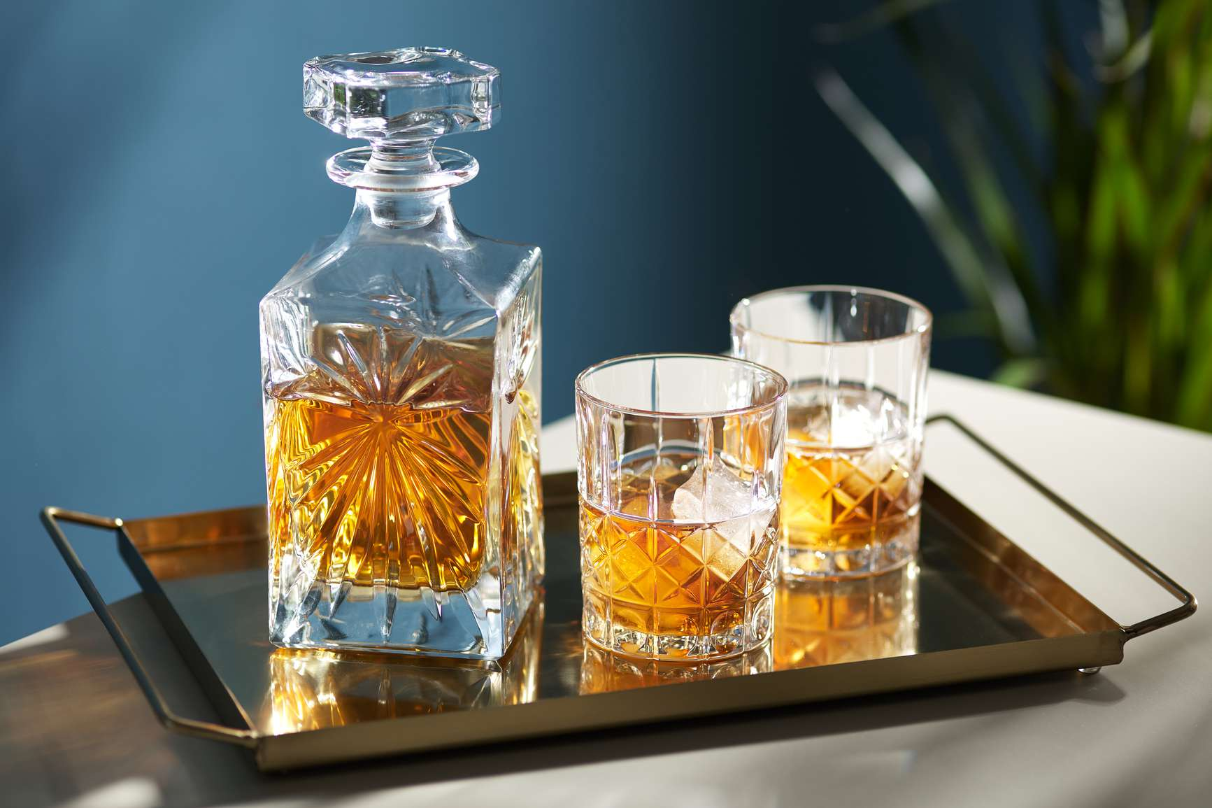 Crystal decanter of whiskey next to two glasses of whisky on a gold tray.