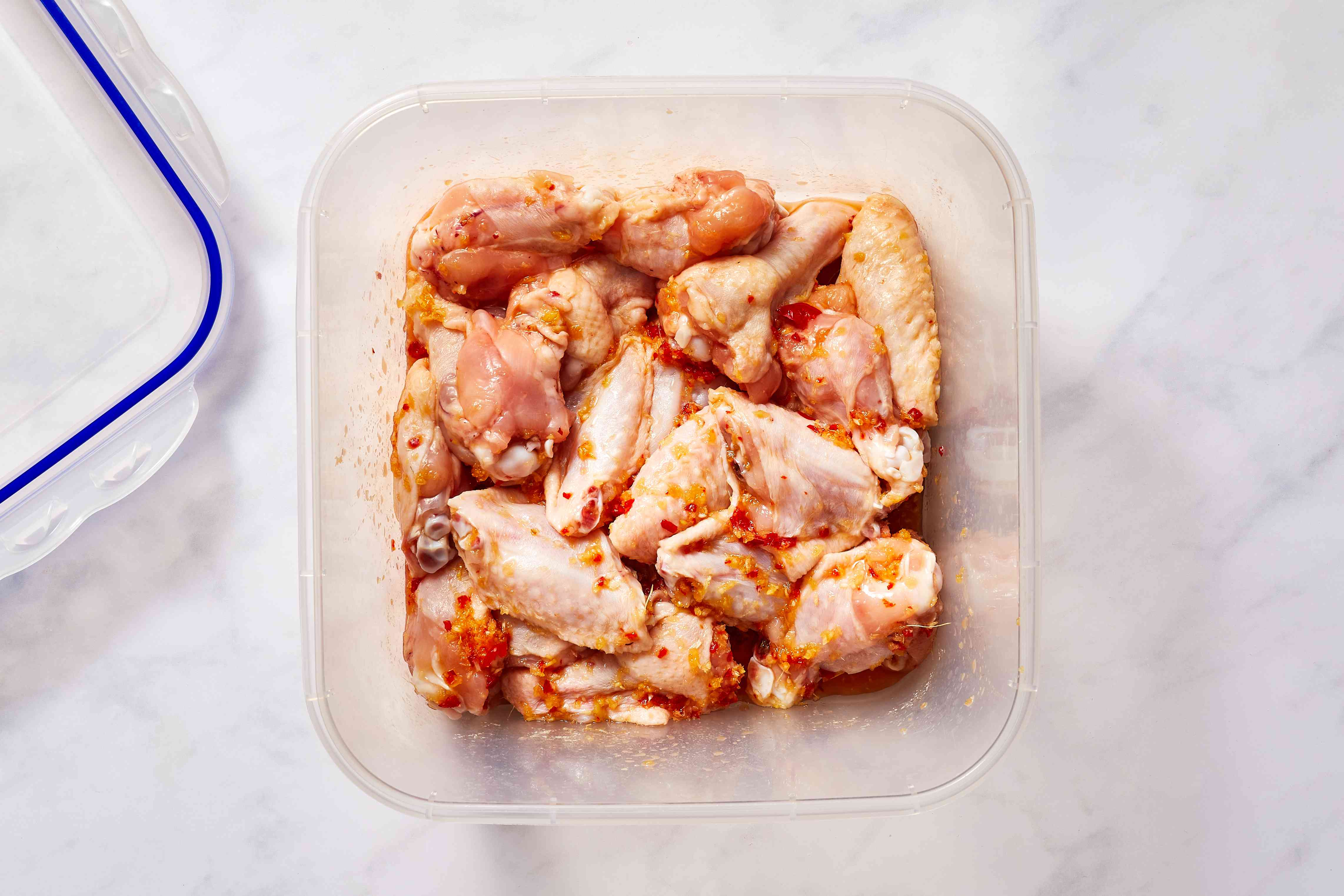chicken wings in a marinade in a container
