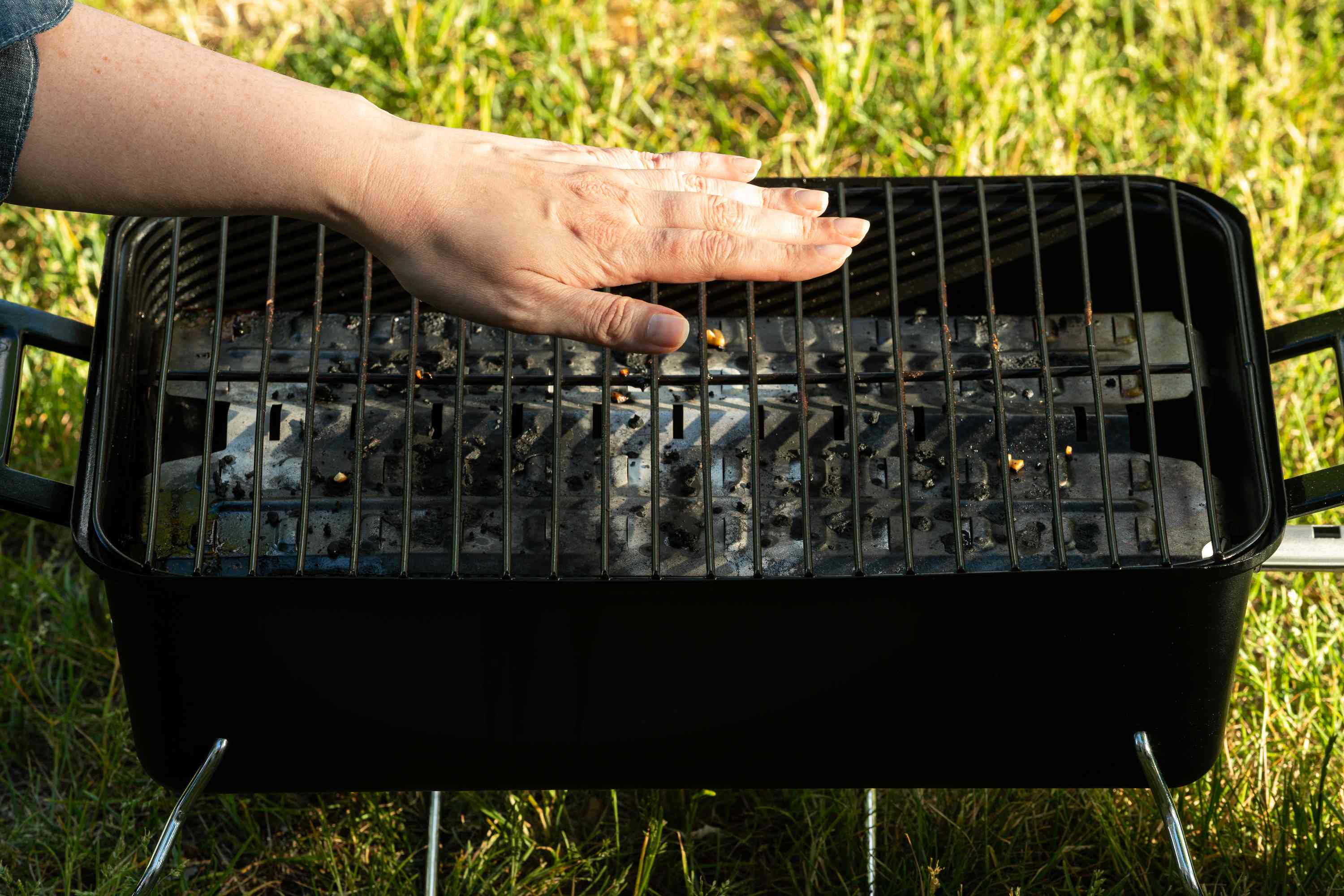 hand over charcoal grill to test temperature of grill