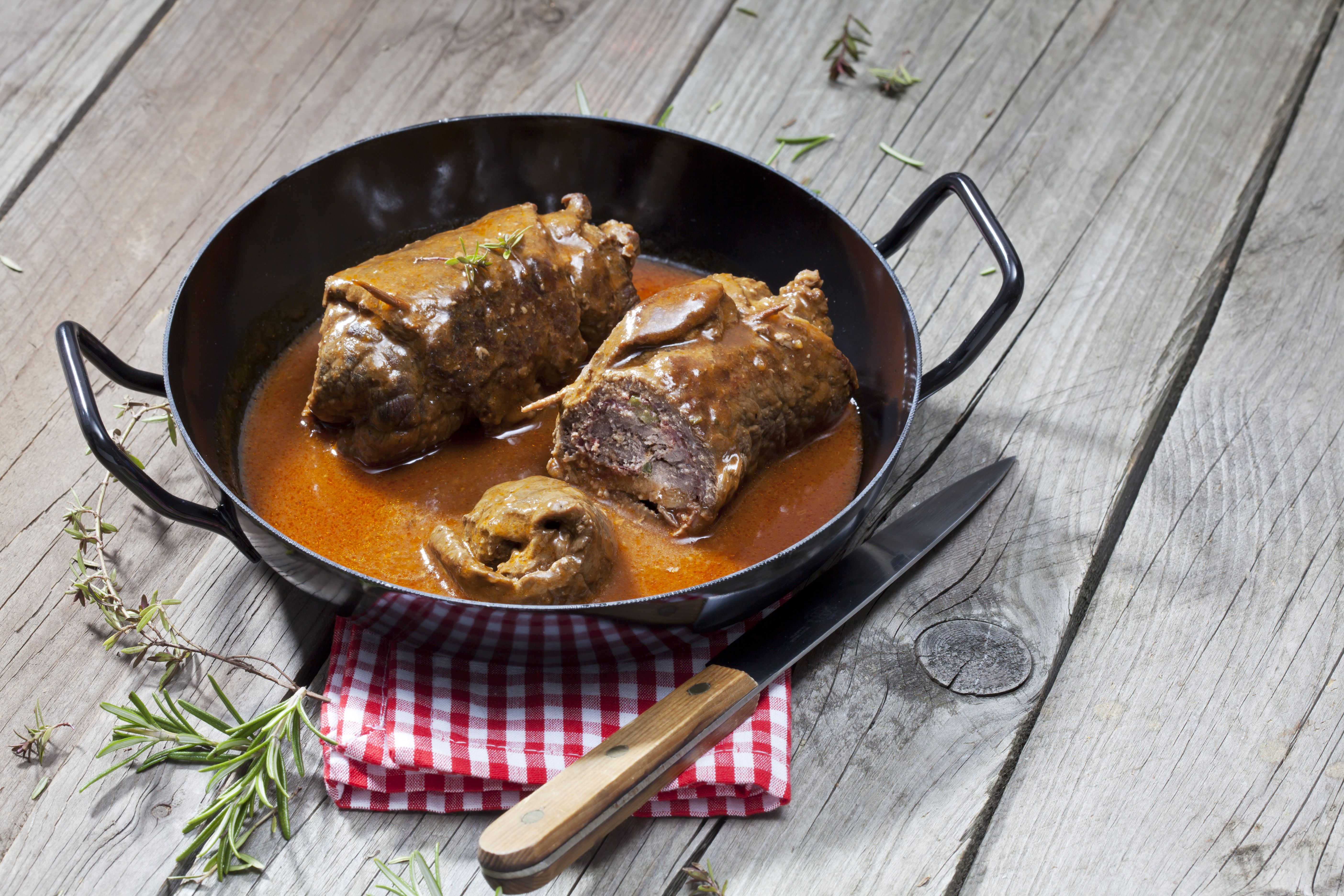 Beef roulades in braising pan, rosemary, kitchen towel and knife on wood