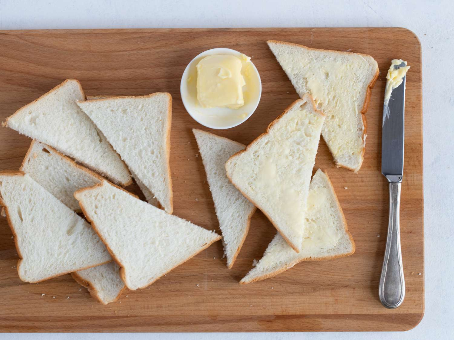 Spreading butter onto bread slices for pudding