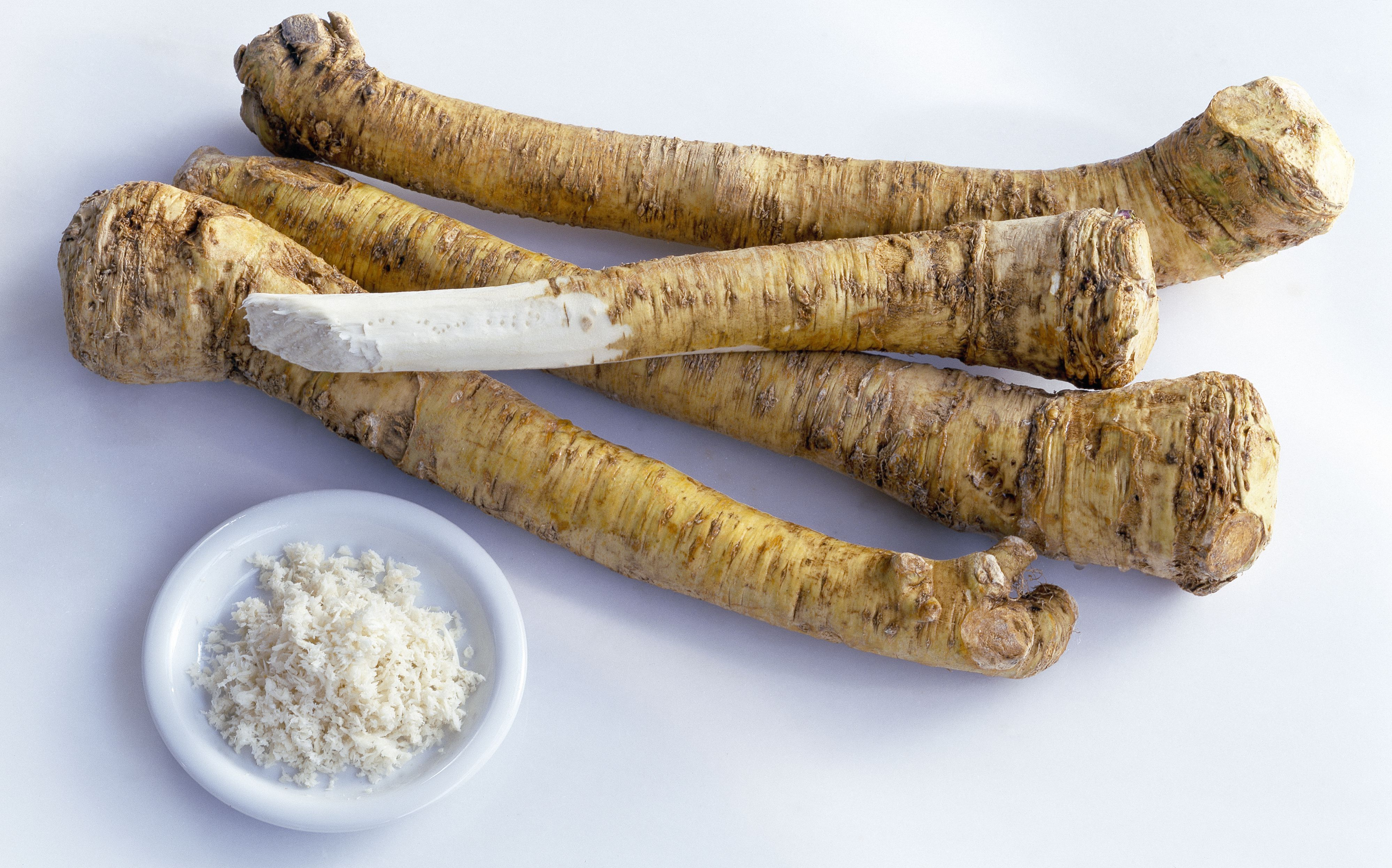 Four sticks of horseradish and bowl of grated horseradish