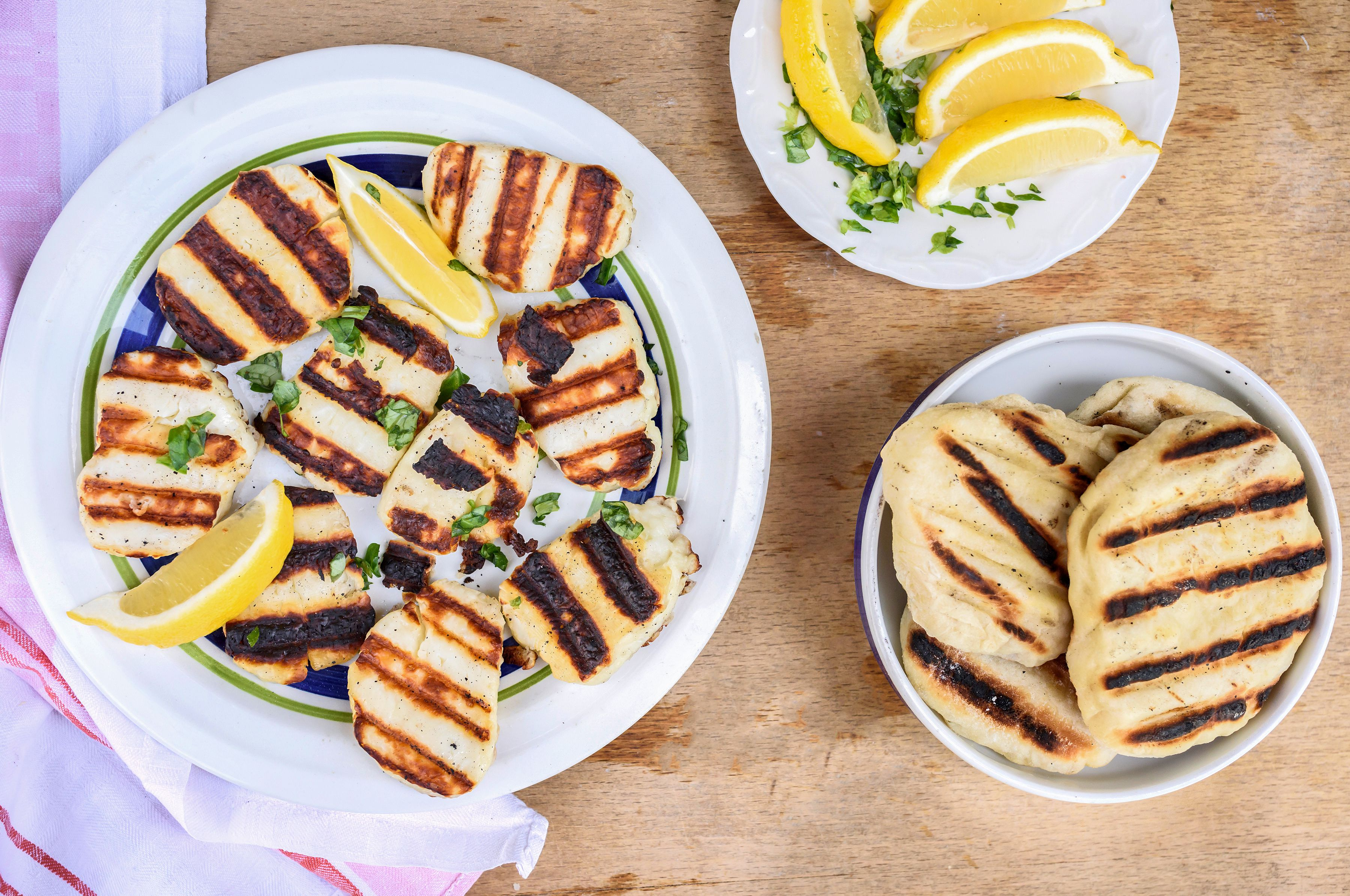 Grilled halloumi cheese on a plate with lemon wedges and herbs