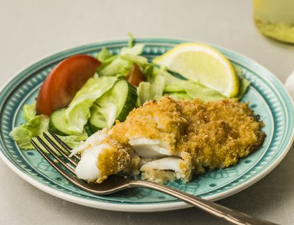 Parmesan baked fish on a plate with salad and lemon wedge