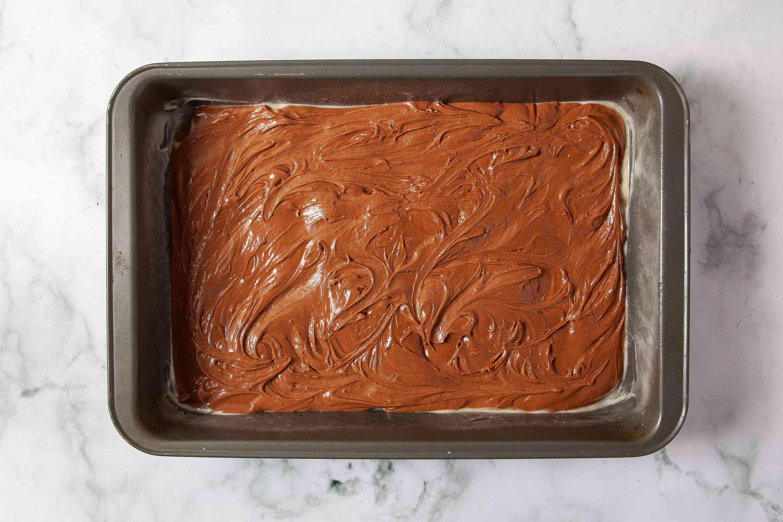 Half of brownie batter in a pan
